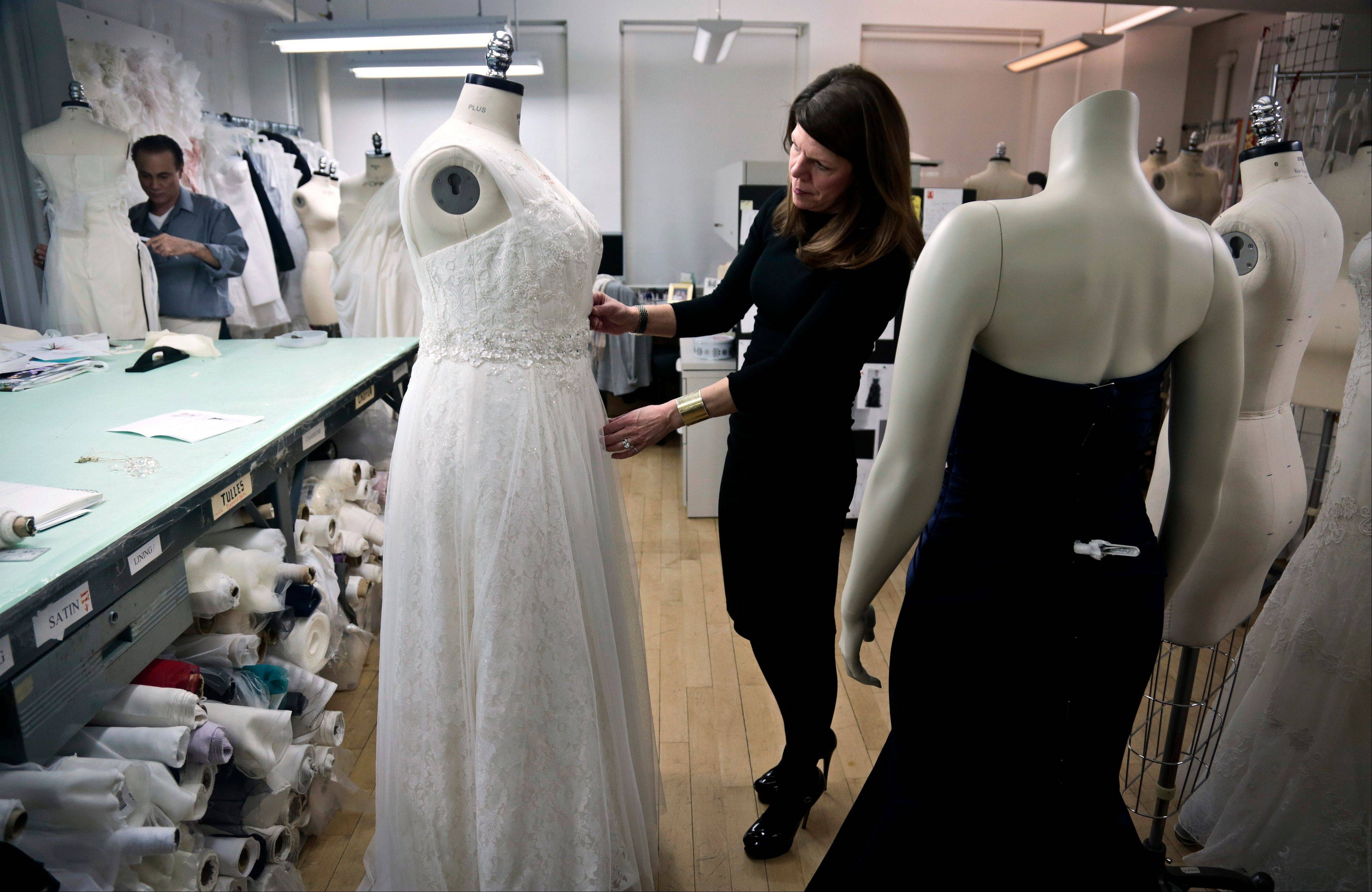 David's Bridal senior vice president Michele von Plato, right, arranges a dress on a plus-size mannequin in New York. David's Bridal, the nation's largest bridal chain, started changing its fit mannequins used to create gowns to reflect the average body.