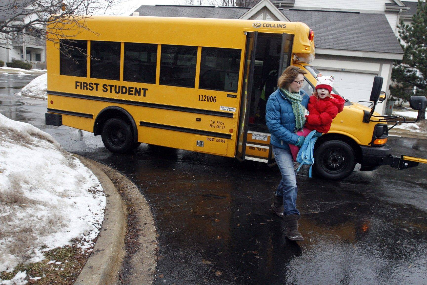 Associated Press Debbie Jurcak, a mother of three, carries her 4-year-old daughter Ella off the school bus after preschool outside their apartment in Aurora. Jurcak, 43, was among many Americans who lost unemployment benefits in late December. On the verge of eviction, she and her husband sought the help of faith-based organizations to help them pay rent.