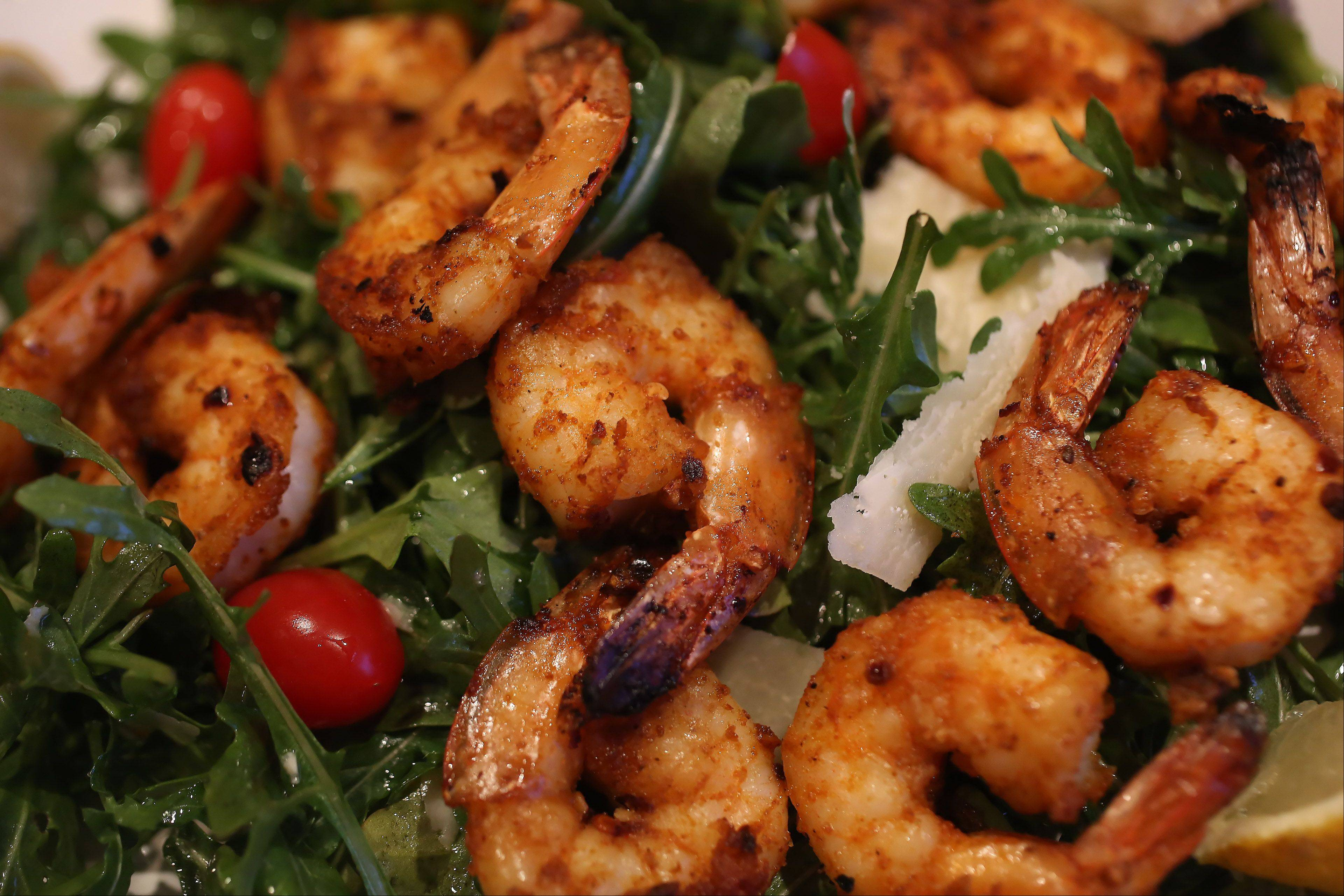 Theresa Zagnoli and her son Joe, 10, top a simple arugula salad with spicy shrimp for a quick and healthy meal.