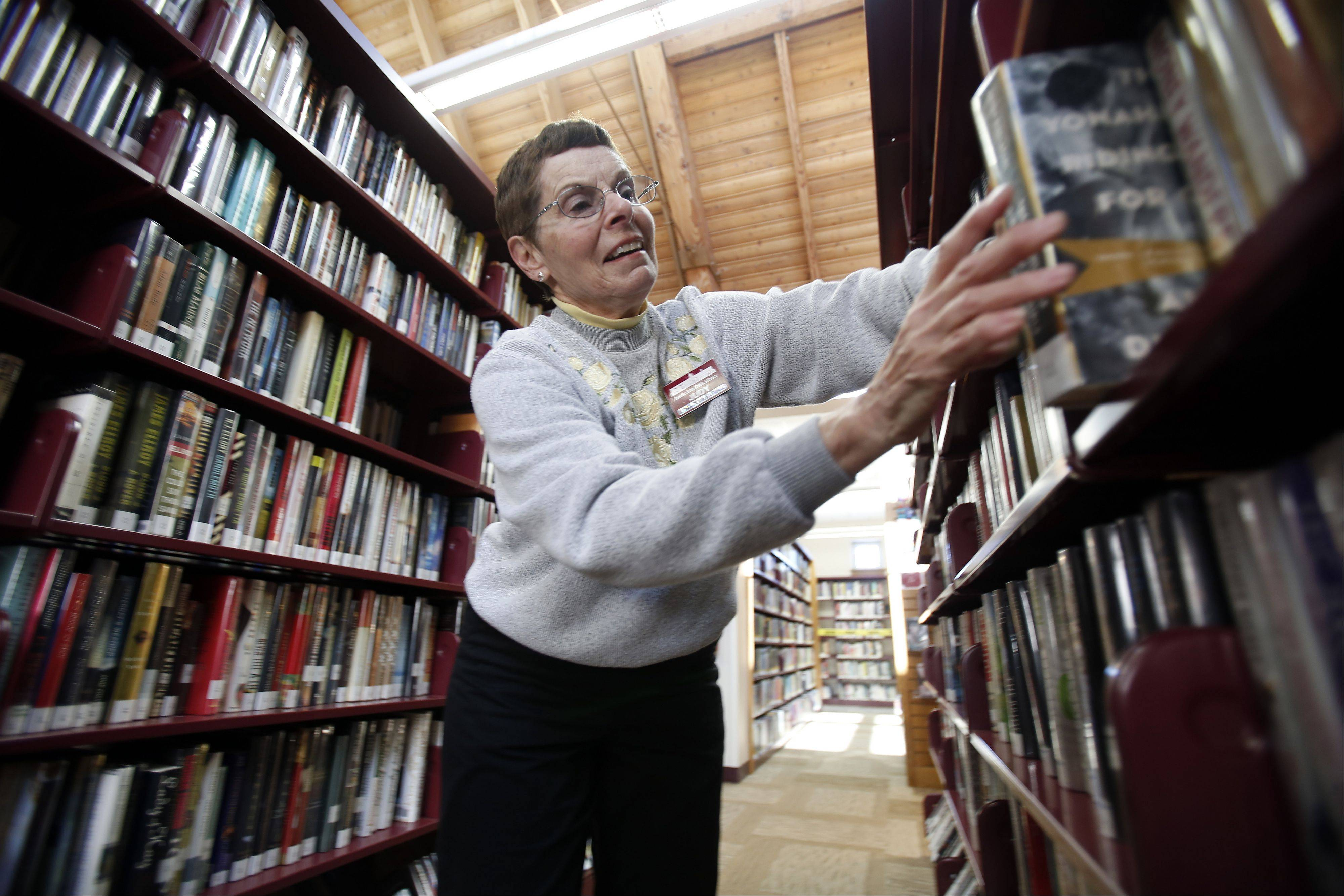 Judy Mulcahy restocks shelves at the Huntley Area Public Library, which celebrates its 25th anniversary this year.