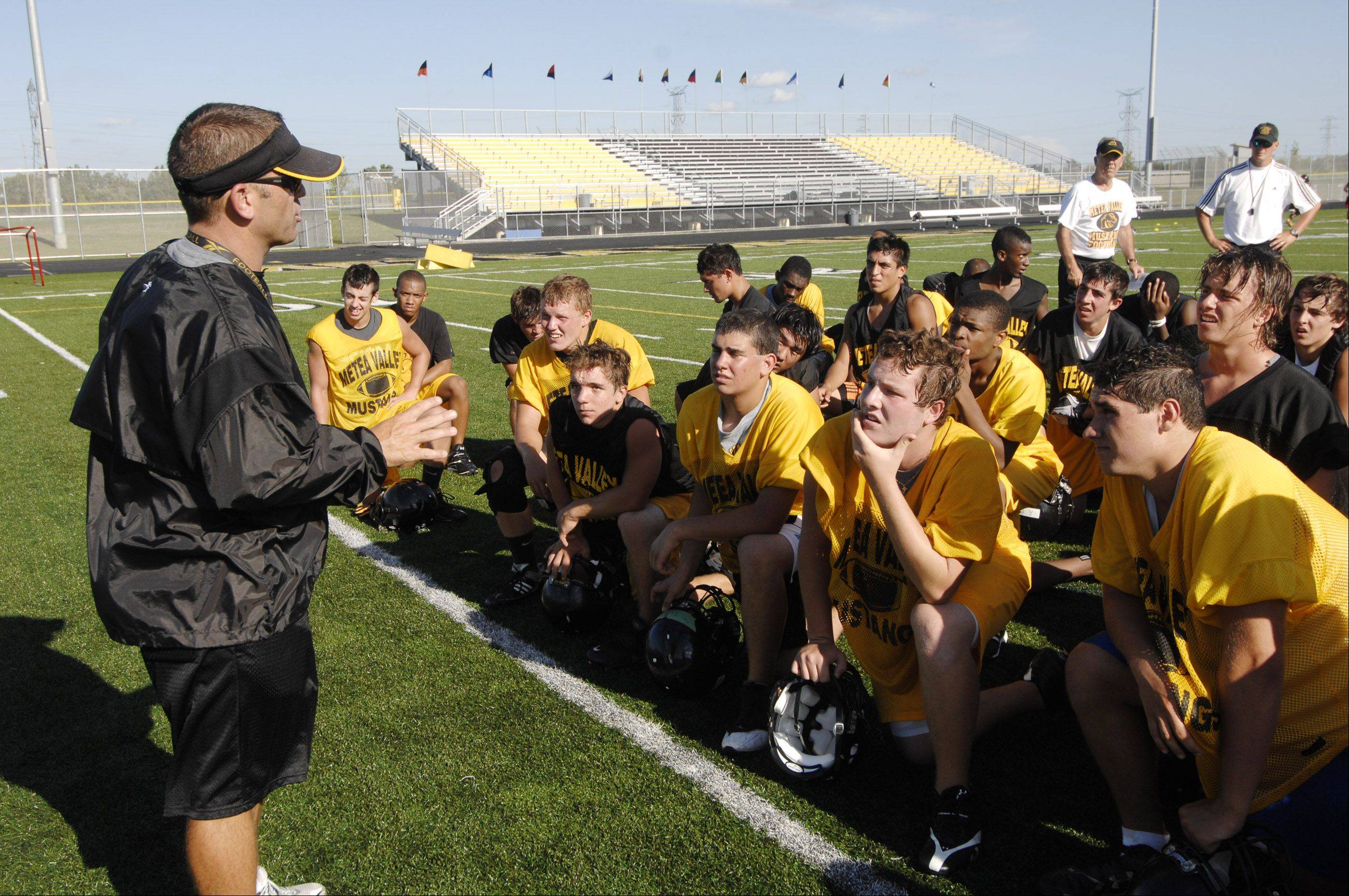 Head Coach Ted Monken addresses players on the first day of practice for Metea Valley High School�s first varsity football squad.
