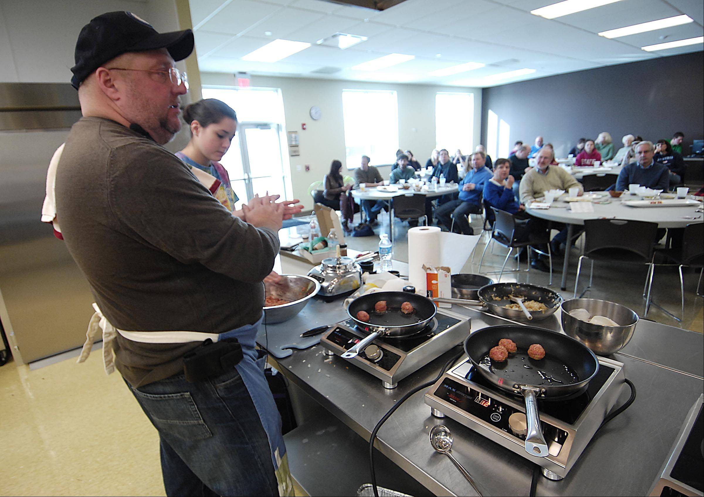 With an assist from Steffany Hagen of Elgin, Daily Herald Cook of the Year Dan Rich makes football-friendly meatballs during a Super Bowl snacks demonstration at the Northern Illinois Food Bank in Geneva.