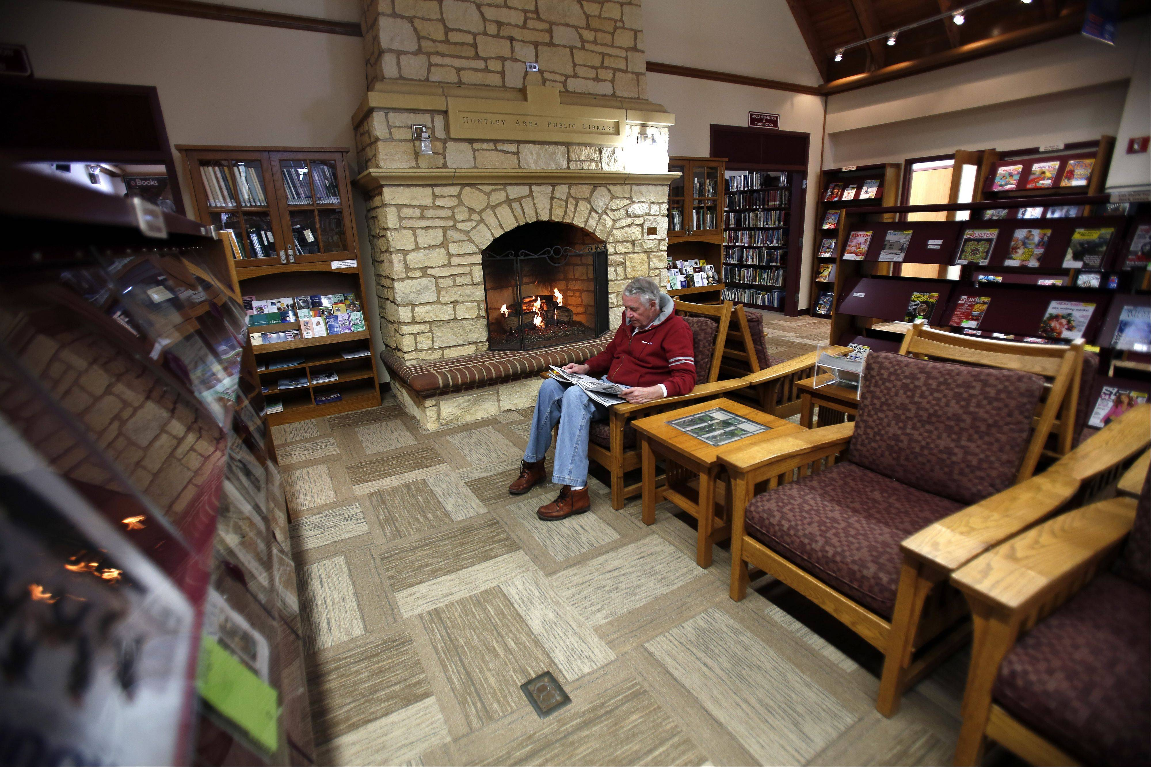 John Cox of Huntley enjoys a newspaper in front of the signature fireplace at the Huntley Area Public Library, which celebrates its 25th anniversary this year.