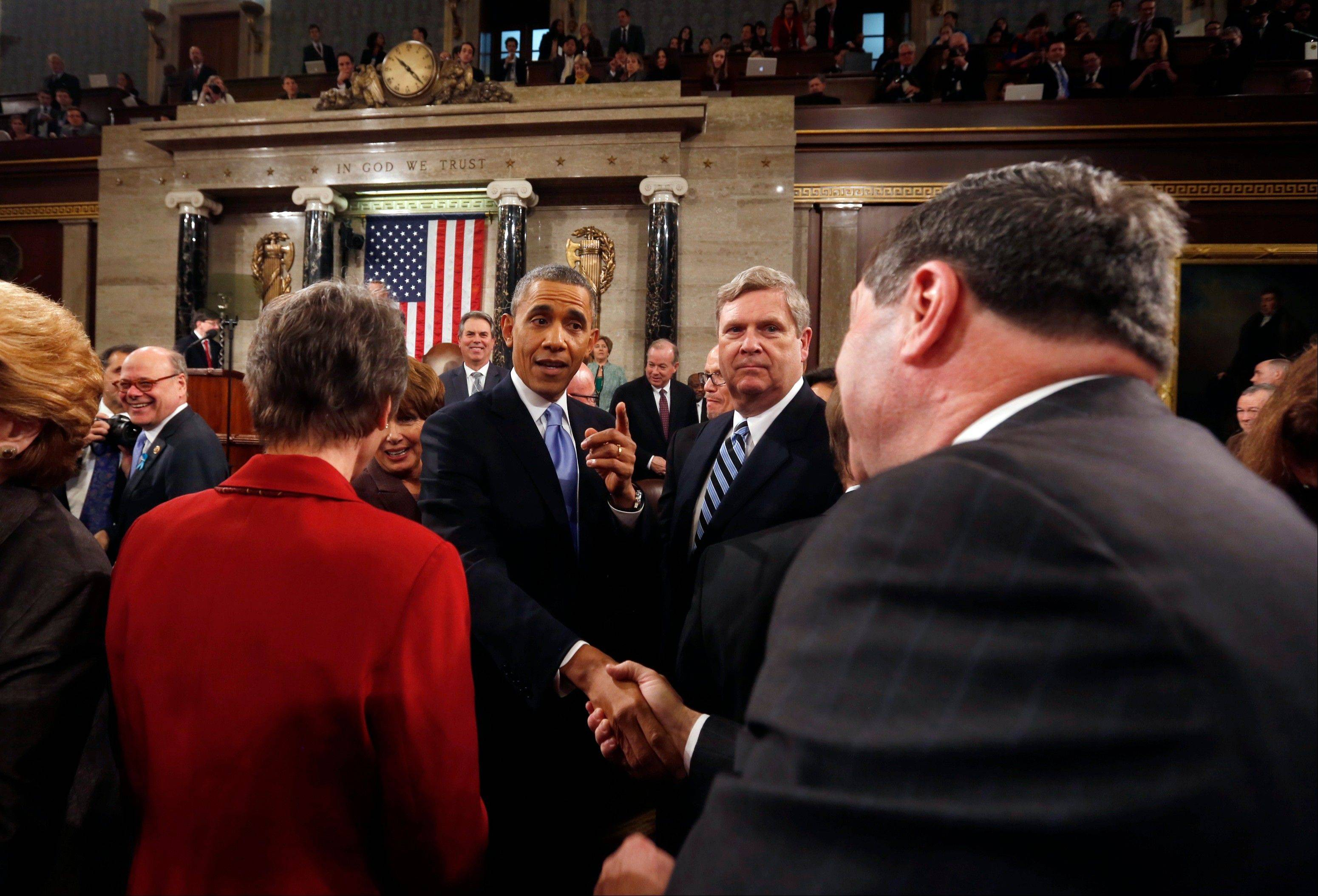President Barack Obama shakes hands as he leaves after giving the State of Union address before a joint session of Congress in the House chamber Tuesday in Washington.