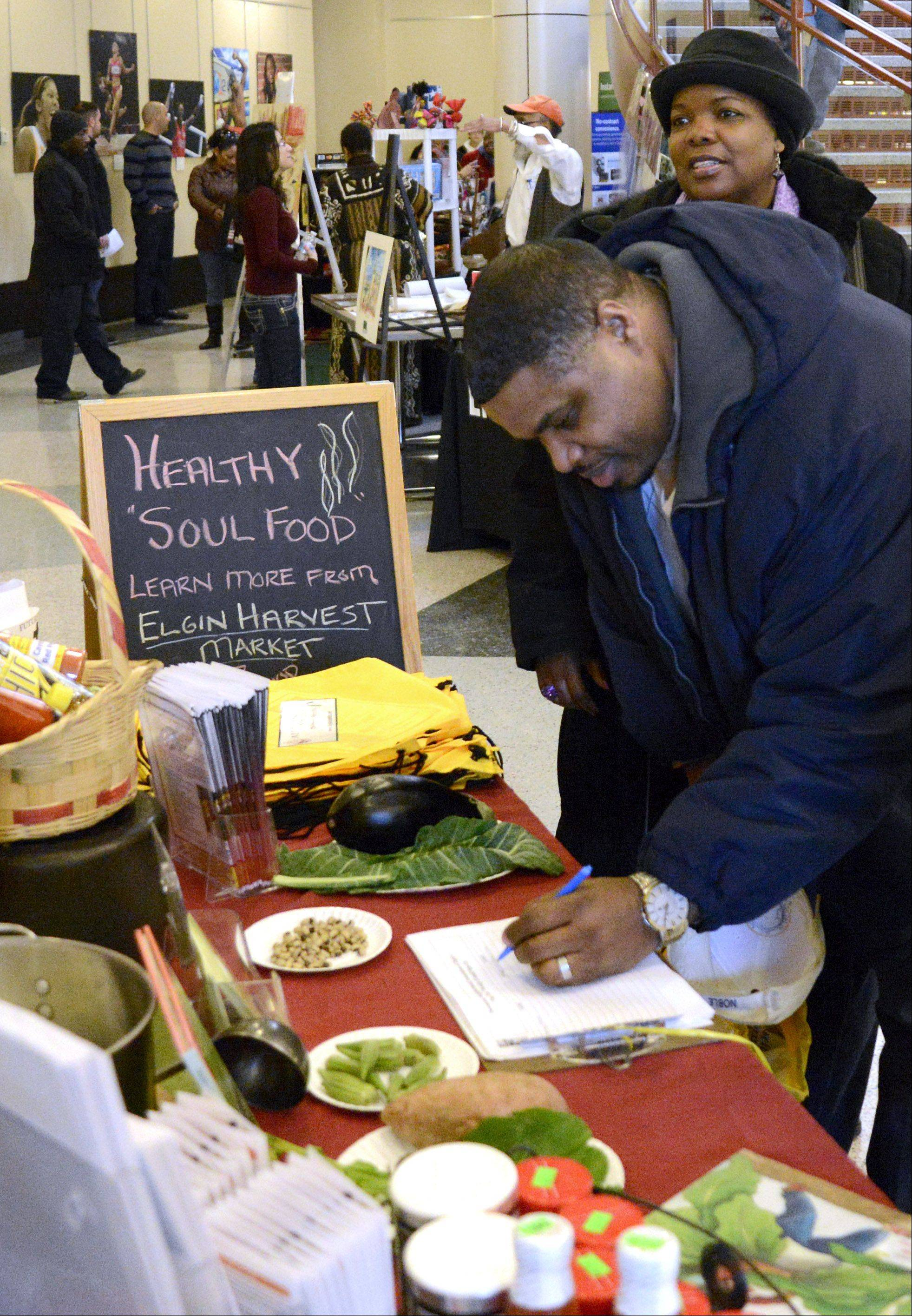 Elgin police Sgt. Gary Neal and his wife, Marilyn, of Huntley sign up to win a basket full of goodies at the Elgin Harvest Market's Healthy Soul Food table at the eighth annual Black History Family Festival at the Gail Borden Public Library in Elgin.