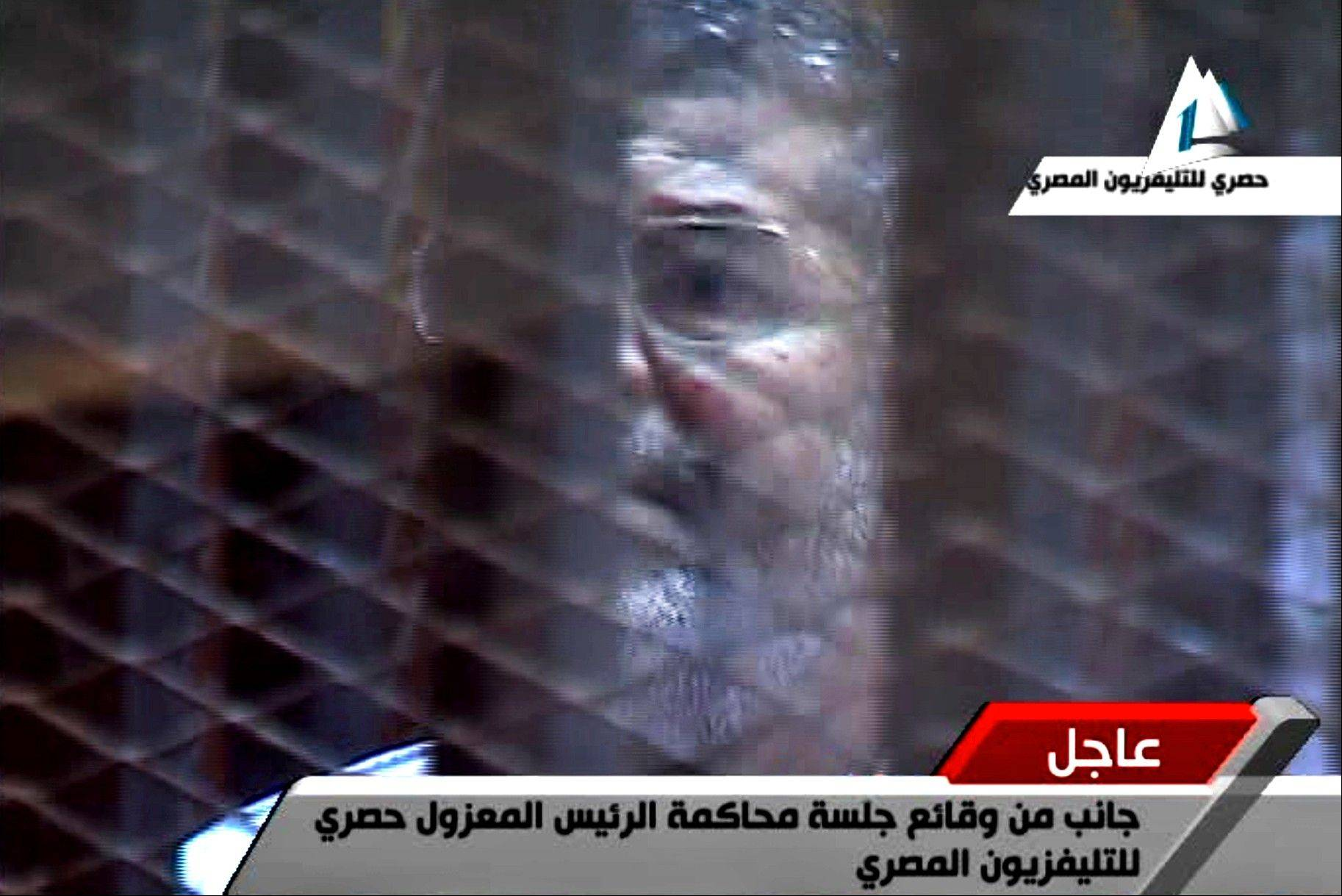 Egypt's toppled President Mohammed Morsi stands inside a glass-encased metal cage in a courtroom in Cairo, Egypt, Tuesday, Jan. 28. 2014. Morsi was separated from other defendants for the start of a new trial Tuesday over charges from prison breaks during the country's 2011 revolution, state television reported.