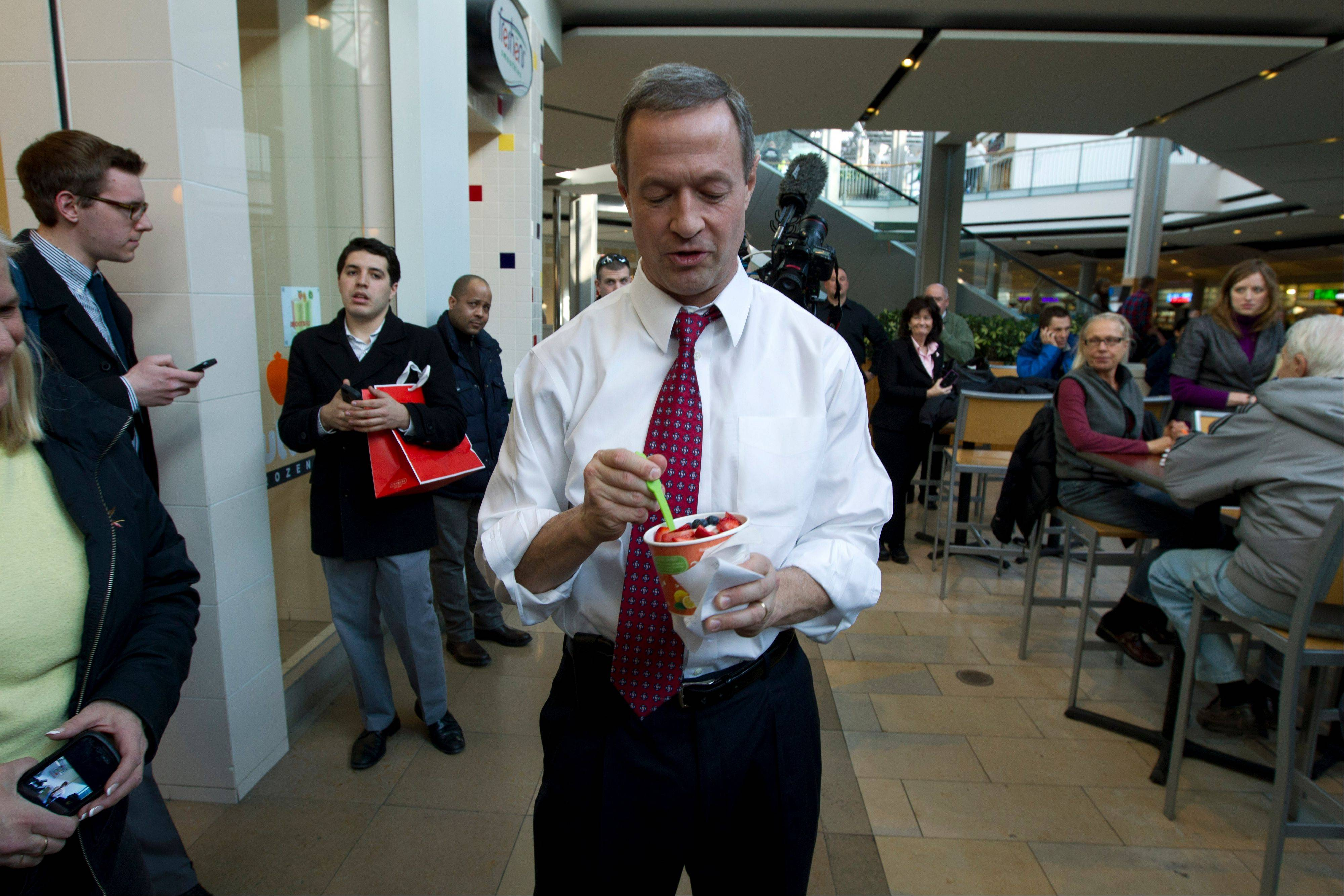Maryland Gov. Martin O'Malley, eats frozen yogurt as he tour the Mall in Columbia, Md, after the mall was reopened to the public on Monday Jan. 27, 2014. Three people died Saturday in a shooting at a mall in suburban Baltimore, including the presumed gunman.