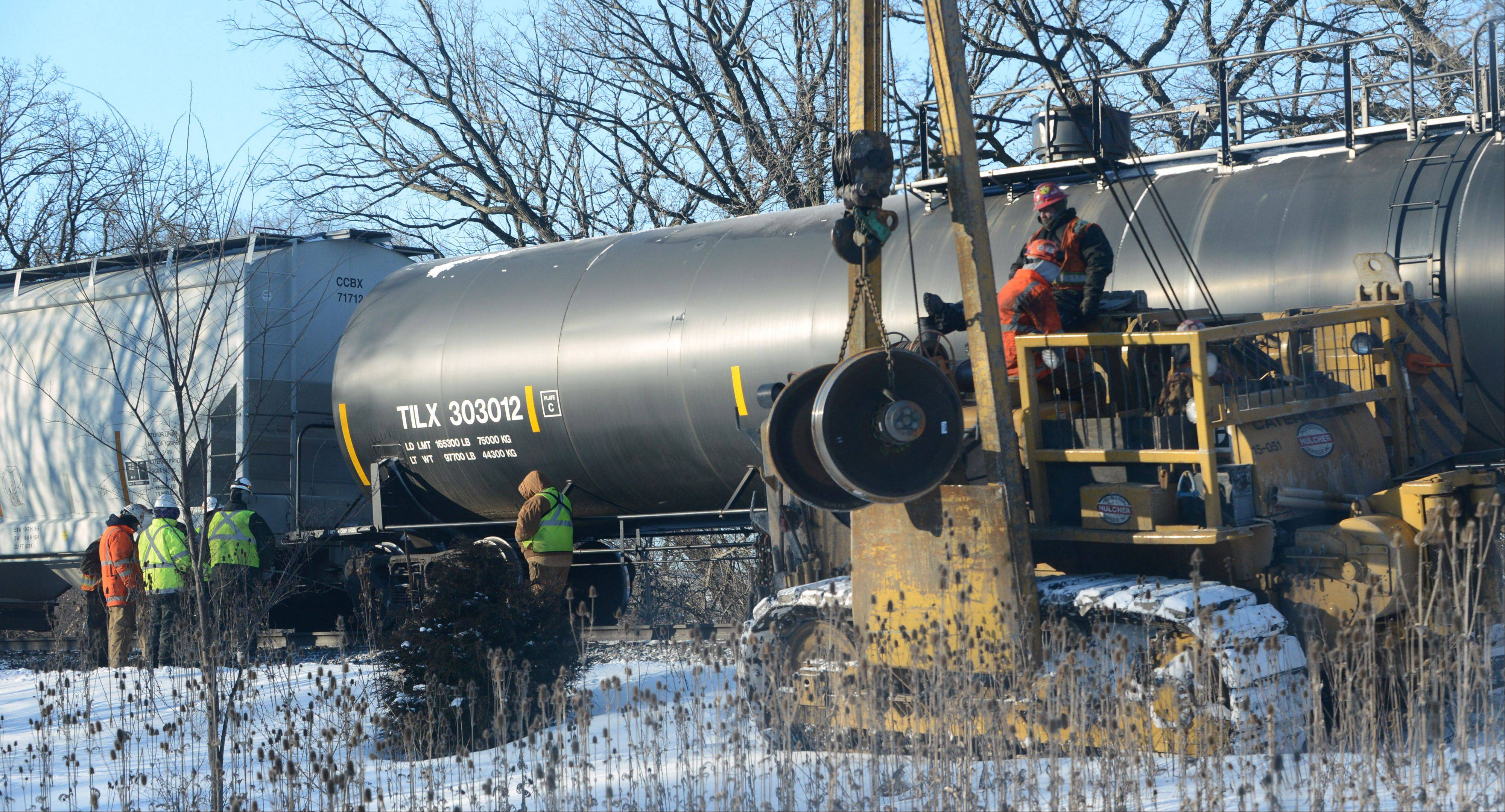 Canadian National crews work at a derailment at the Route 45 overpass between Route 176 and Winchester Road in Mundelein Tuesday morning. The derailment caused major delays for Metra commuters.