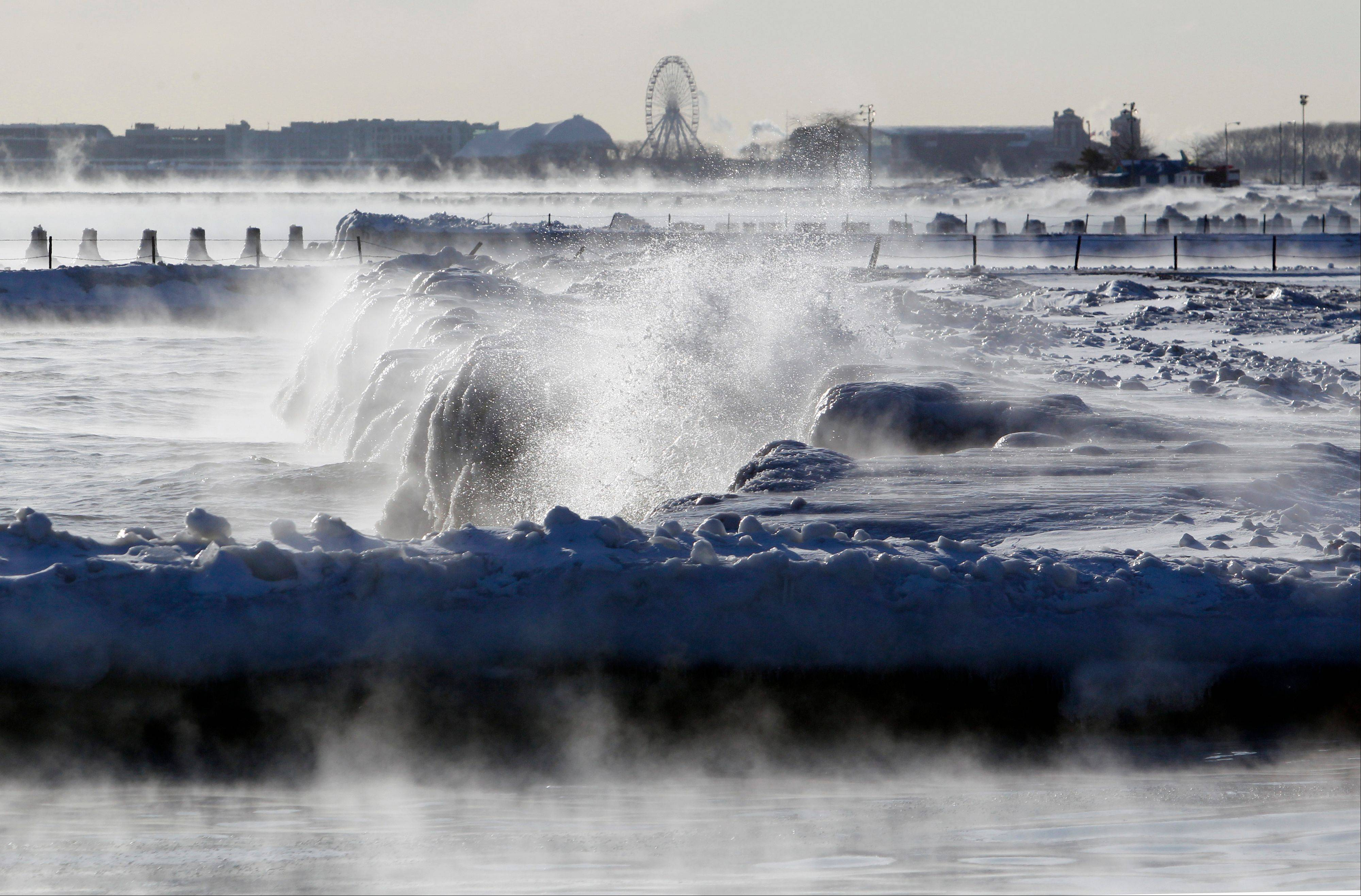 Ice forms as waves crash along the lake shore as Navy Pier's Ferris wheel is seen in the background Monday in Chicago. Below-zero high temperatures have returned to many parts of the Midwest bringing with it wind chills ranging from the negative teens to minus 40s.