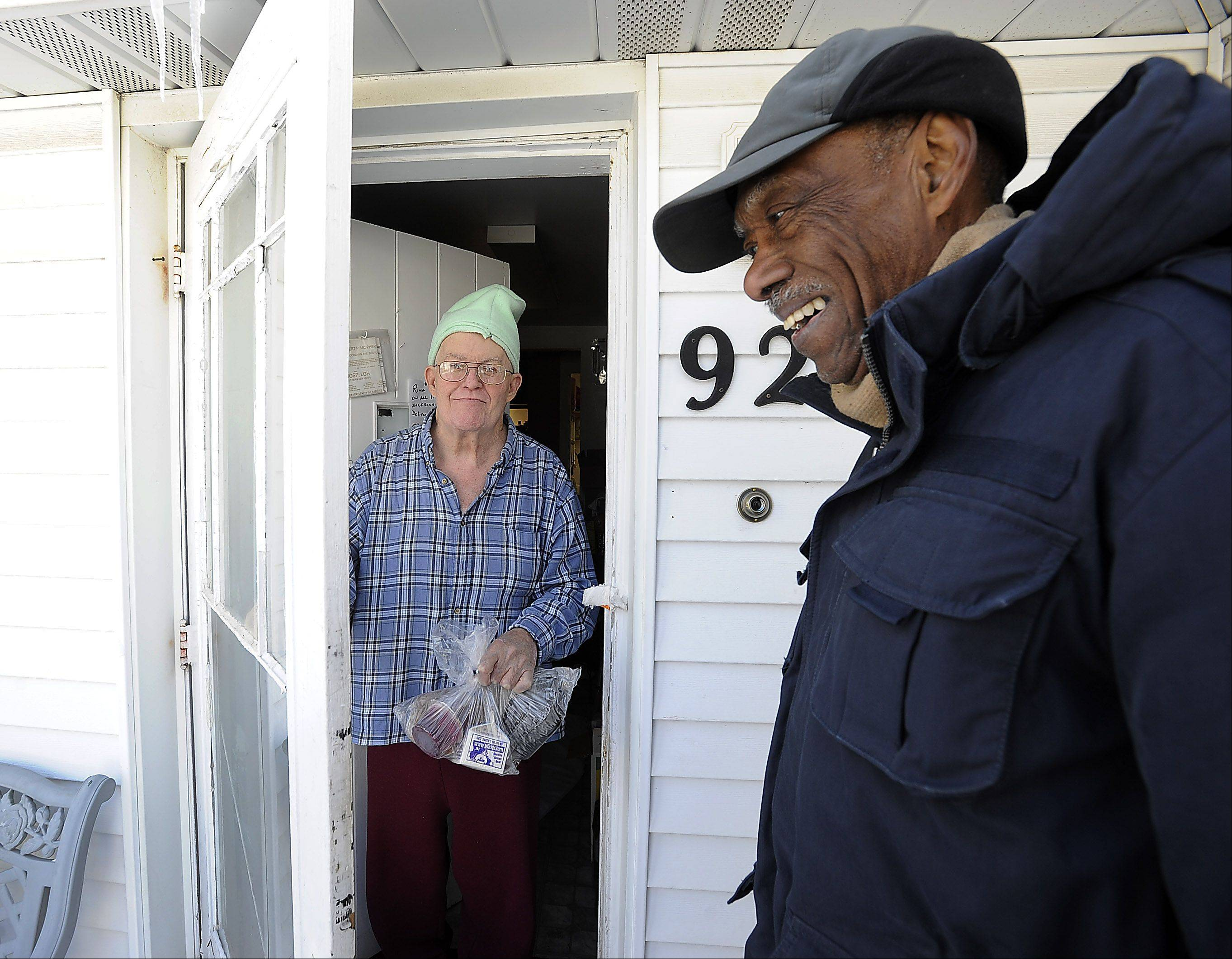 Meals on Wheels volunteer Samuel Grimes, 88, shares a laugh with Robert McPheron, 71, of Des Plaines, after delivering his lunch during Monday's brutal cold.