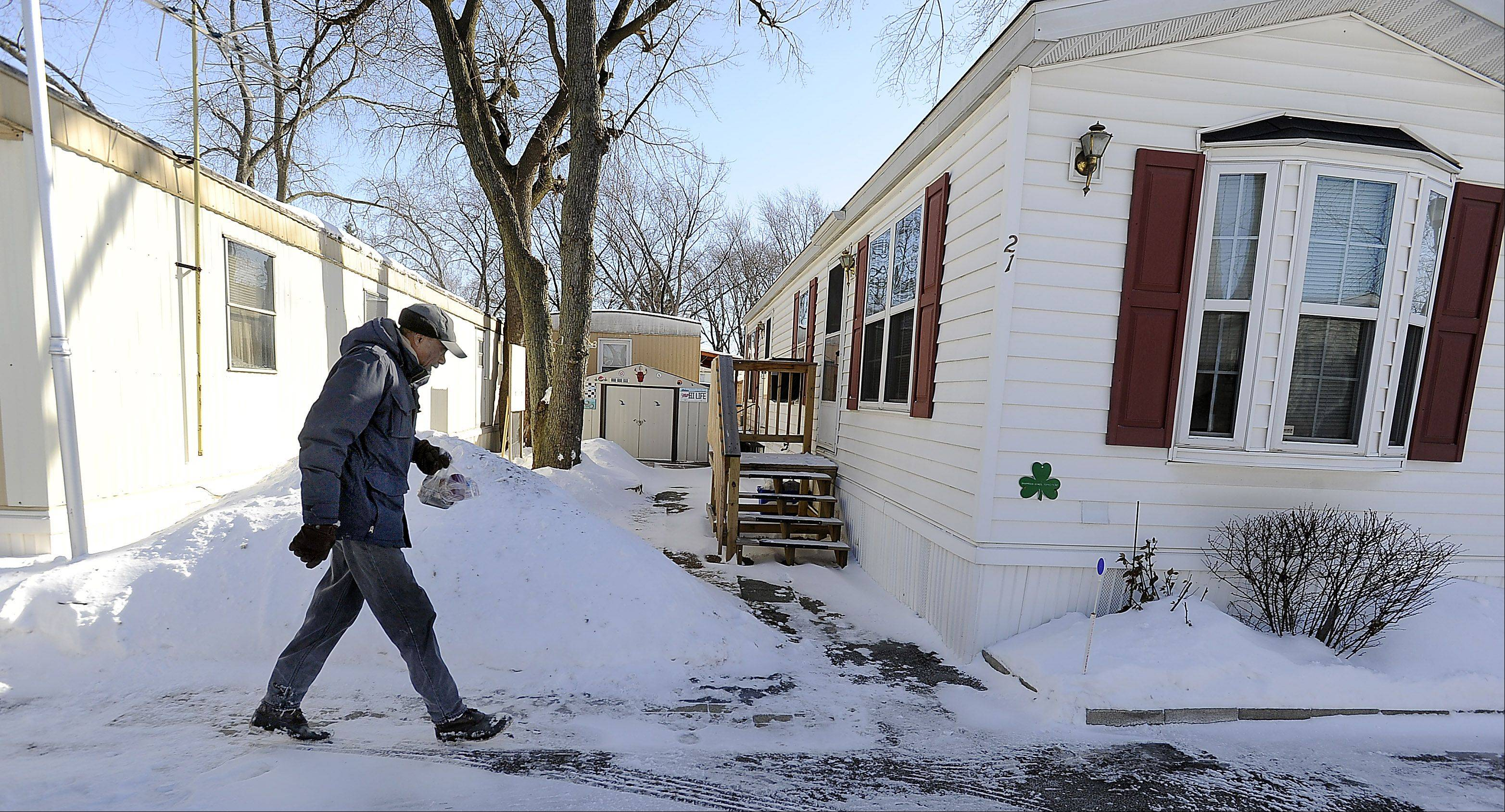 Meals on Wheels driver Samuel Grimes, 88, walks through the snow in a Des Plaines mobile home community Monday to deliver hot meals to needy people on his route.