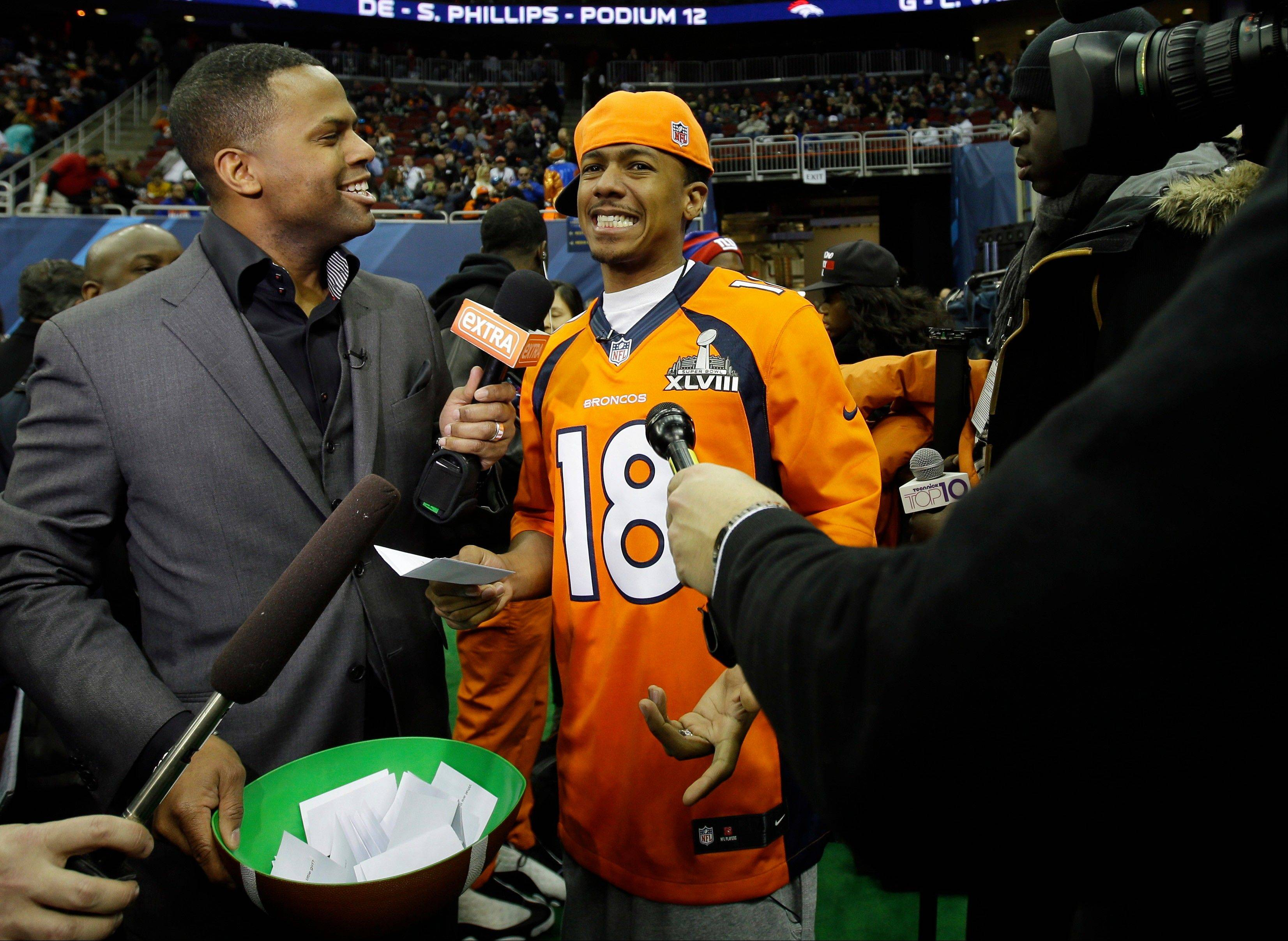 """America's Got Talent"" host Nick Cannon, showing support for the Denver Broncos, is interviewed during media day for the NFL Super Bowl XLVIII football game Tuesday, Jan. 28, 2014, in Newark, N.J."