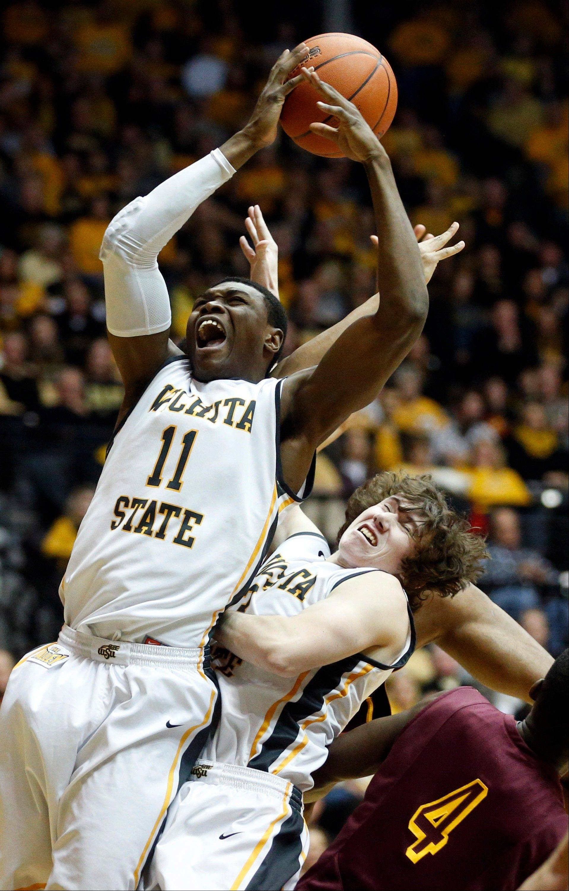 Wichita State forward Cleanthony Early (11) and Evan Wessel (3) go up for a rebound against Loyola during Tuesday night's game in Wichita, Kan.