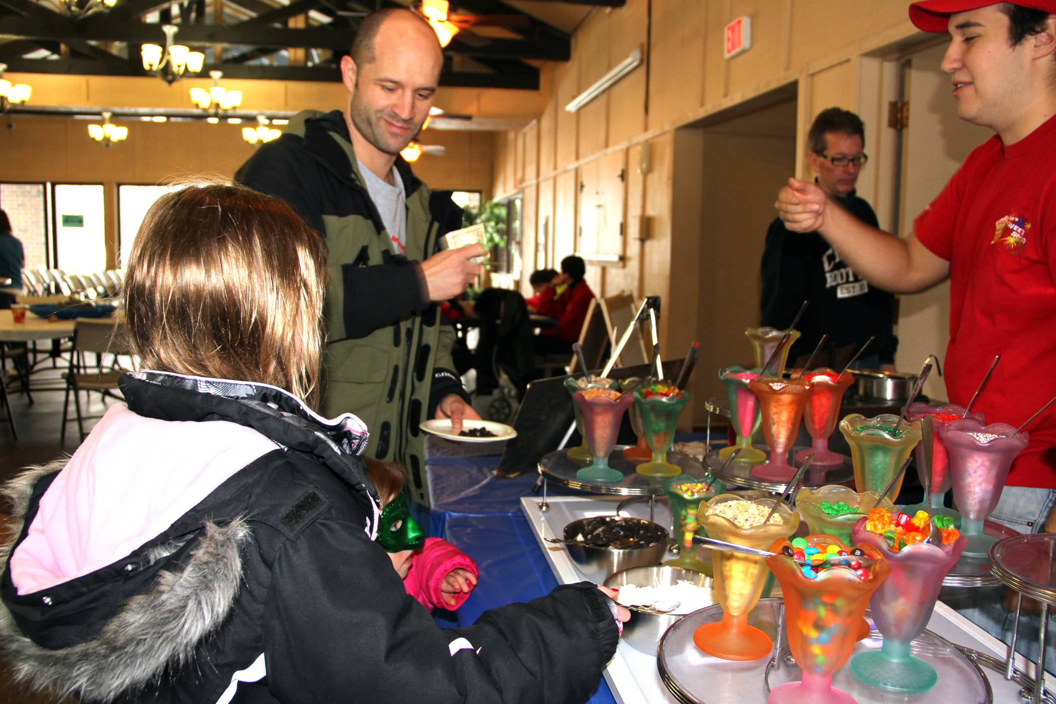 Sean Hayden, of Hinsdale, indulges his daughters at the Winterfest Sweets table during last year's celebration. Concessions, hot chocolate and hot wine will be available for purchase during Oak Brook Park District's Winterfest.