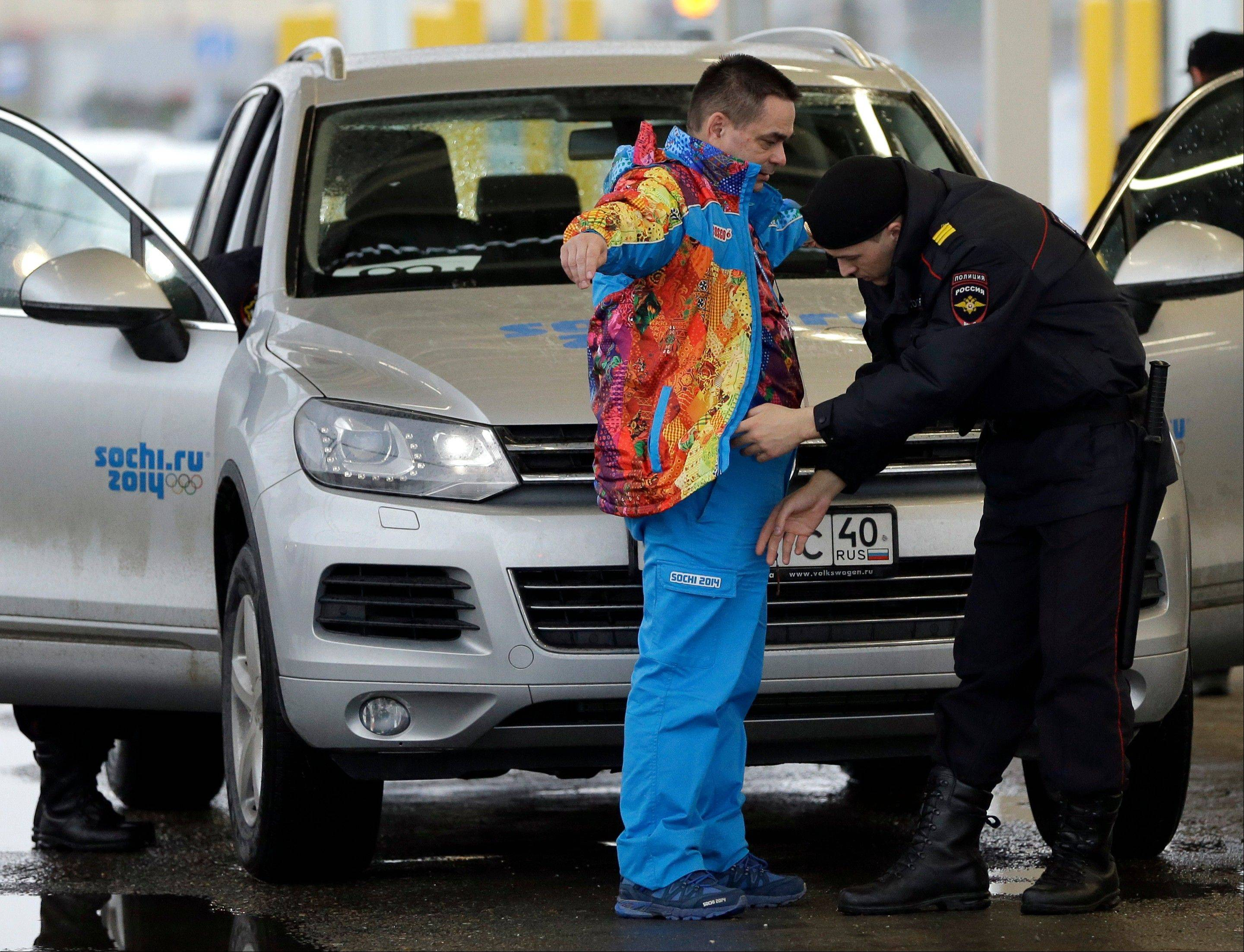 A Russian police officer searches a driver as his vehicle is also screened at an entrance to the Sochi 2014 Olympic Winter Games park, Thursday, Jan. 23, 2014, in Sochi, Russia. The Olympics begin on Feb. 7.