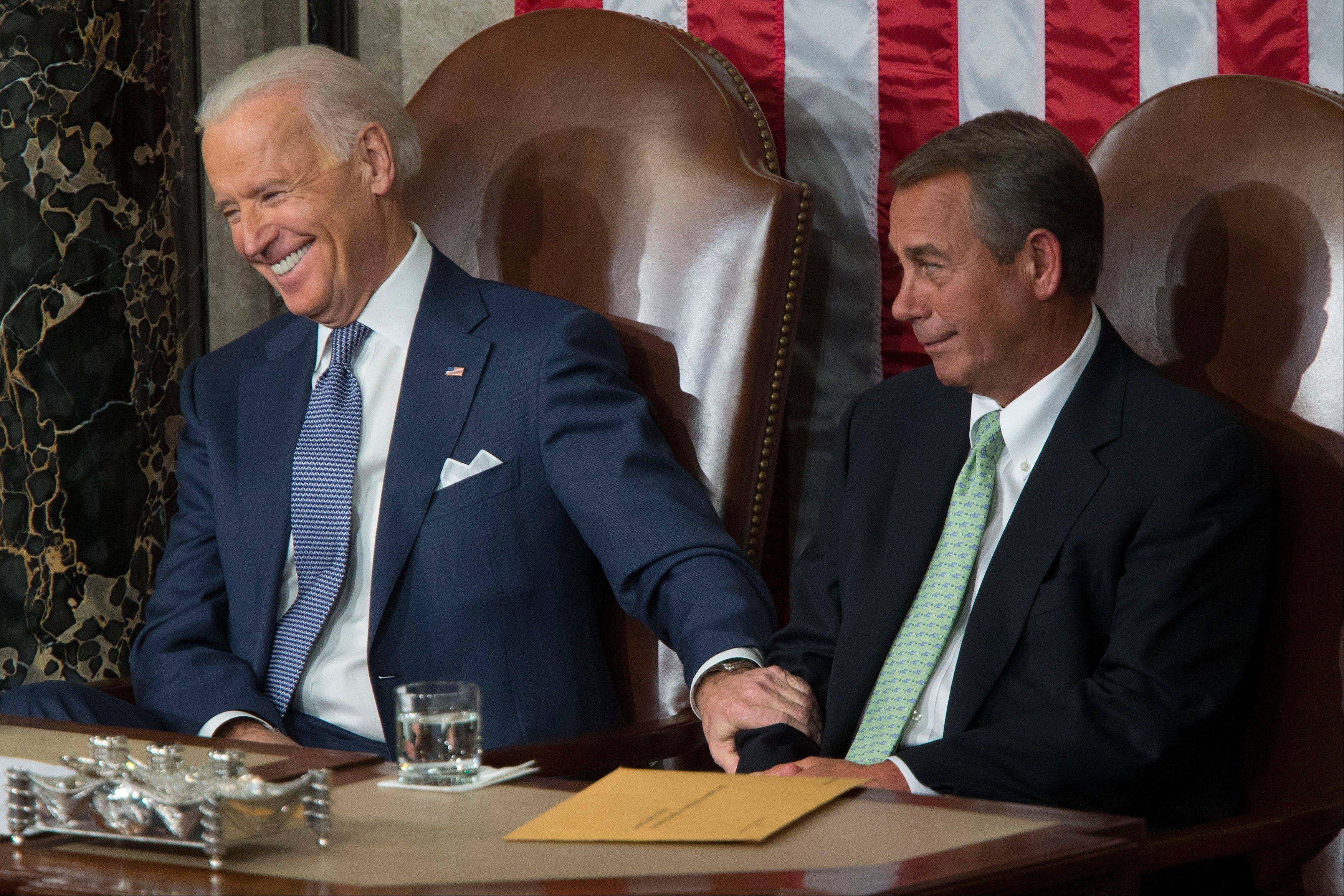 Joseph �Joe� Biden, U.S. vice president, left, holds onto House Speaker John Boehner, a Republican from Ohio, as U.S. President Barack Obama, not pictured, delivers the State of the Union address to a joint session of Congress at the Capitol in Washington, D.C., U.S., on Tuesday, Jan. 28, 2014.
