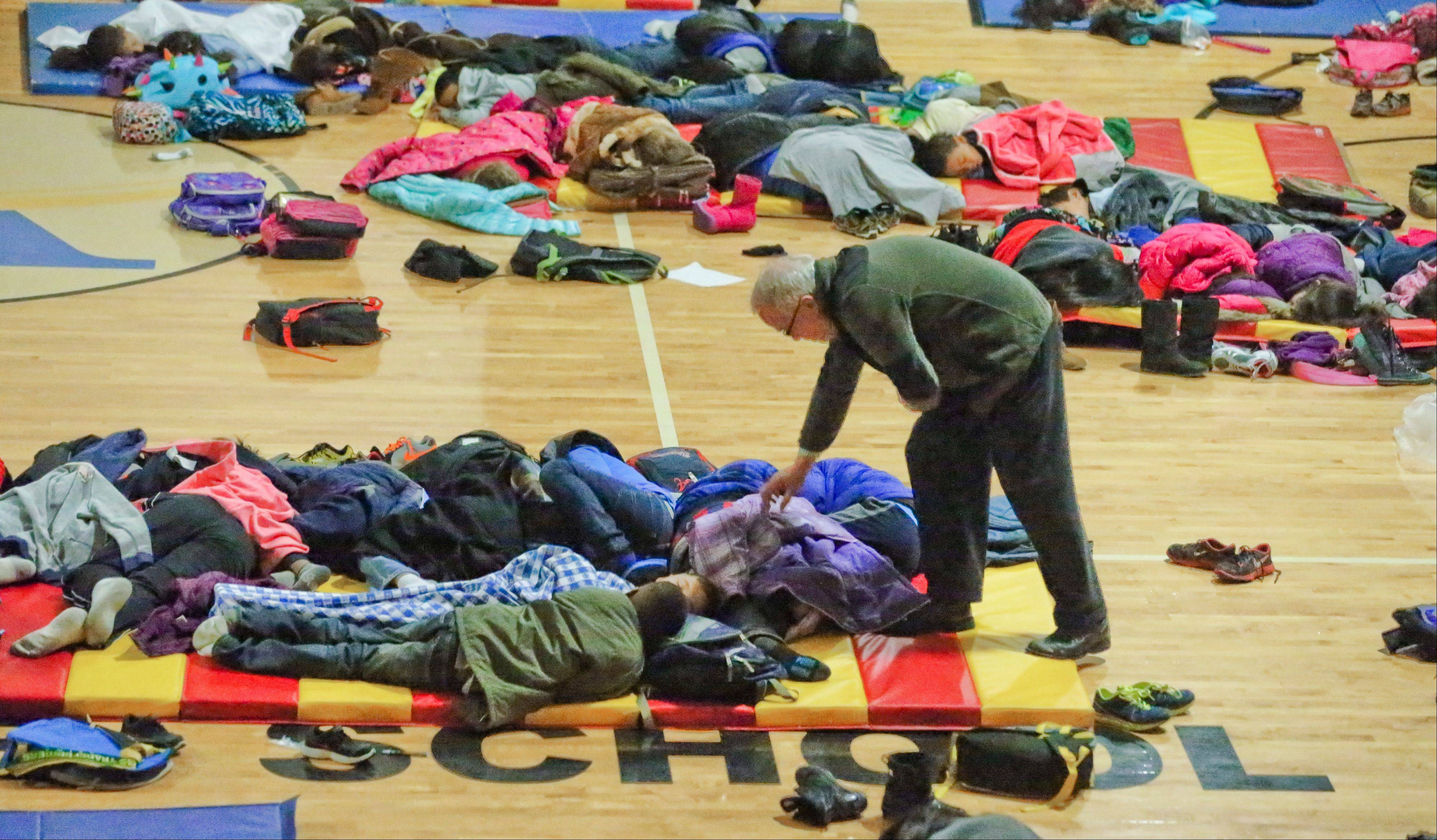 A teacher at E. Rivers Elementary school covers sleeping children in the gym Wednesday in Atlanta. A rare snowstorm left thousands across the South frozen in their tracks, with workers sleeping in their offices, students camping in their schools and commuters abandoning cars along the highway to seek shelter in churches or even grocery stores.