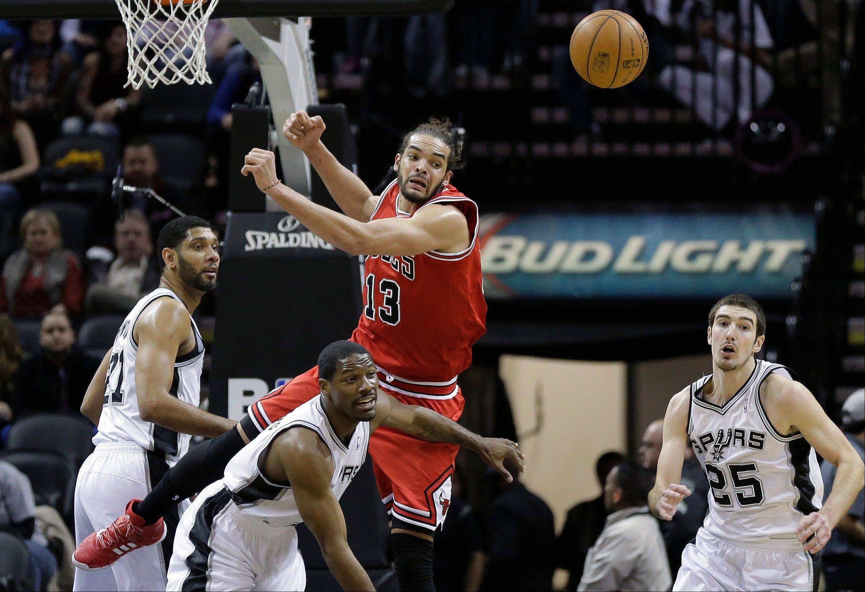 The Bulls� Joakim Noah jumps over the Spurs� Othyus Jeffers, center, for a loose ball during the first half of Wednesday�s game in San Antonio.