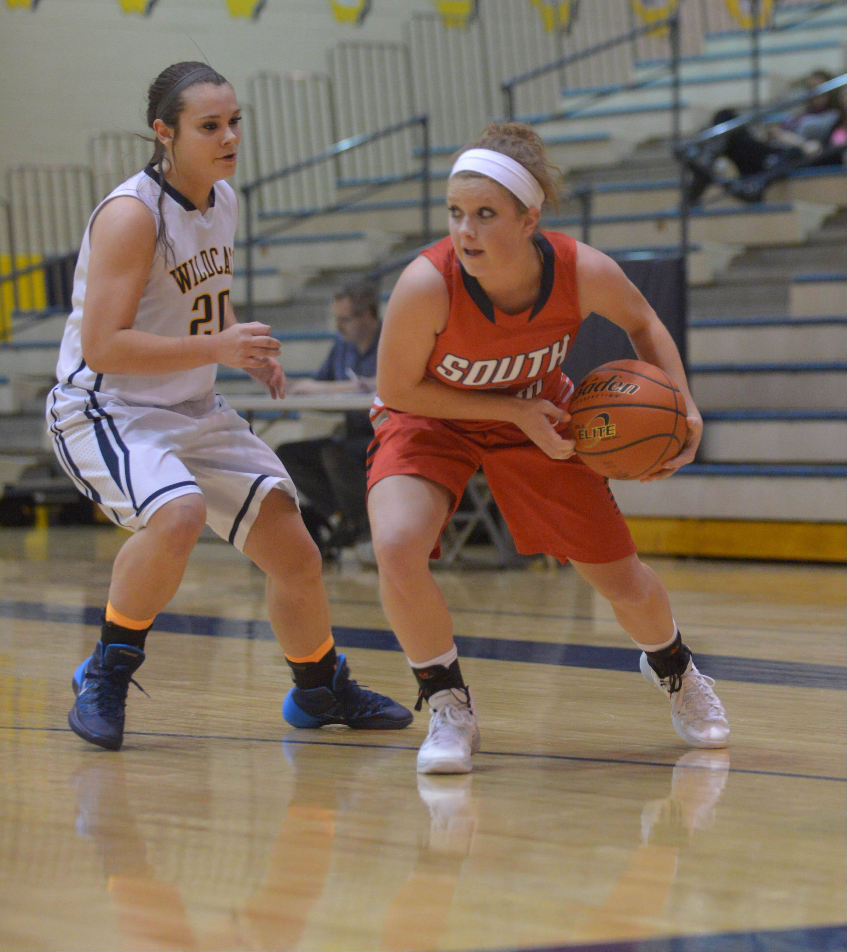 Niki Lazar of Neuqua and Anna Tracy of South Elgin move the ball during the South Elgin at Neuqua Valley girls basketball game Wednesday.