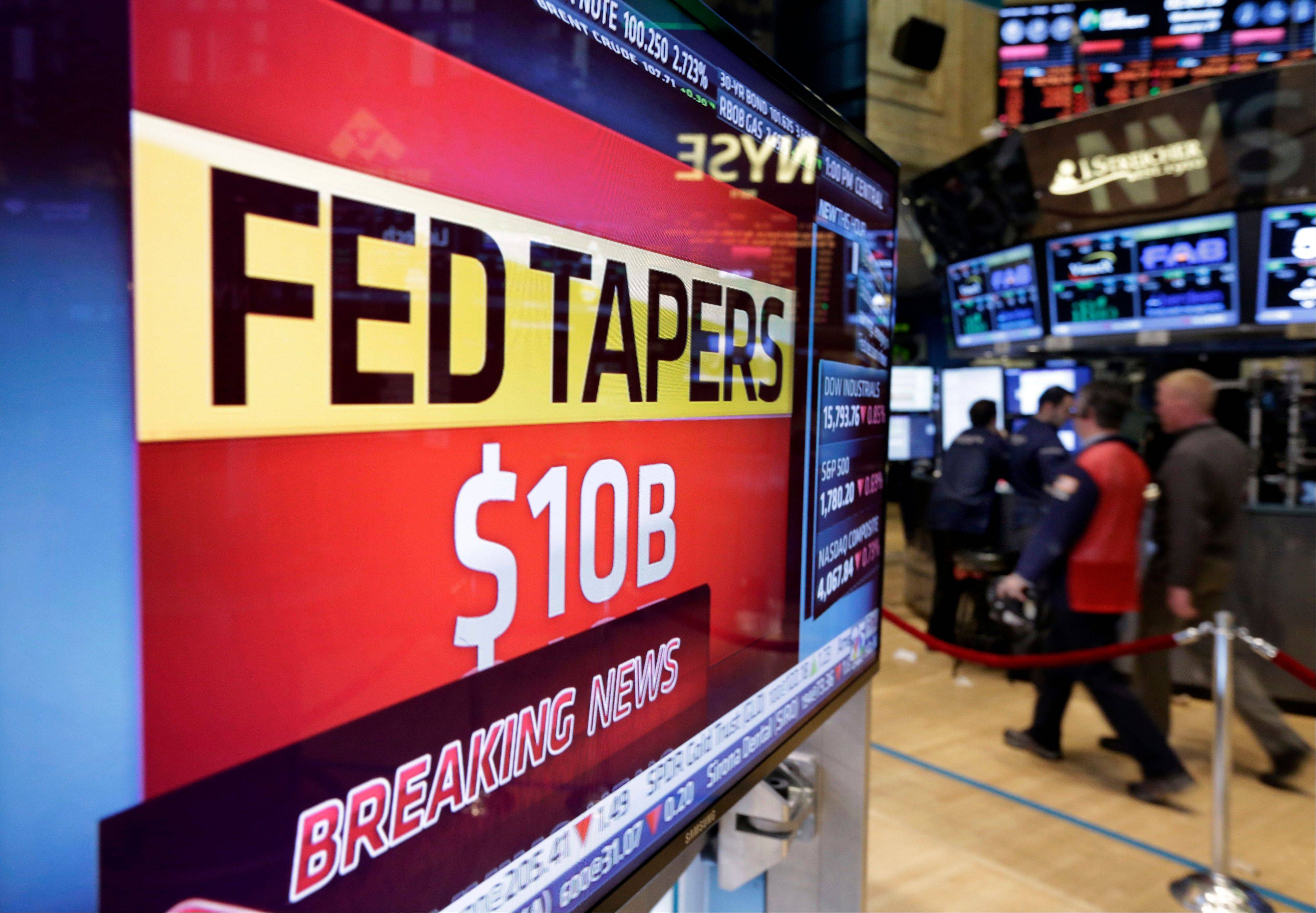 A television screen on the floor of the New York Stock Exchange shows the decision of the Federal Reserve Wednesday, when the central bank said it will cut its monthly bond purchases by an additional $10 billion to $65 billion because of a strengthening U.S. economy.
