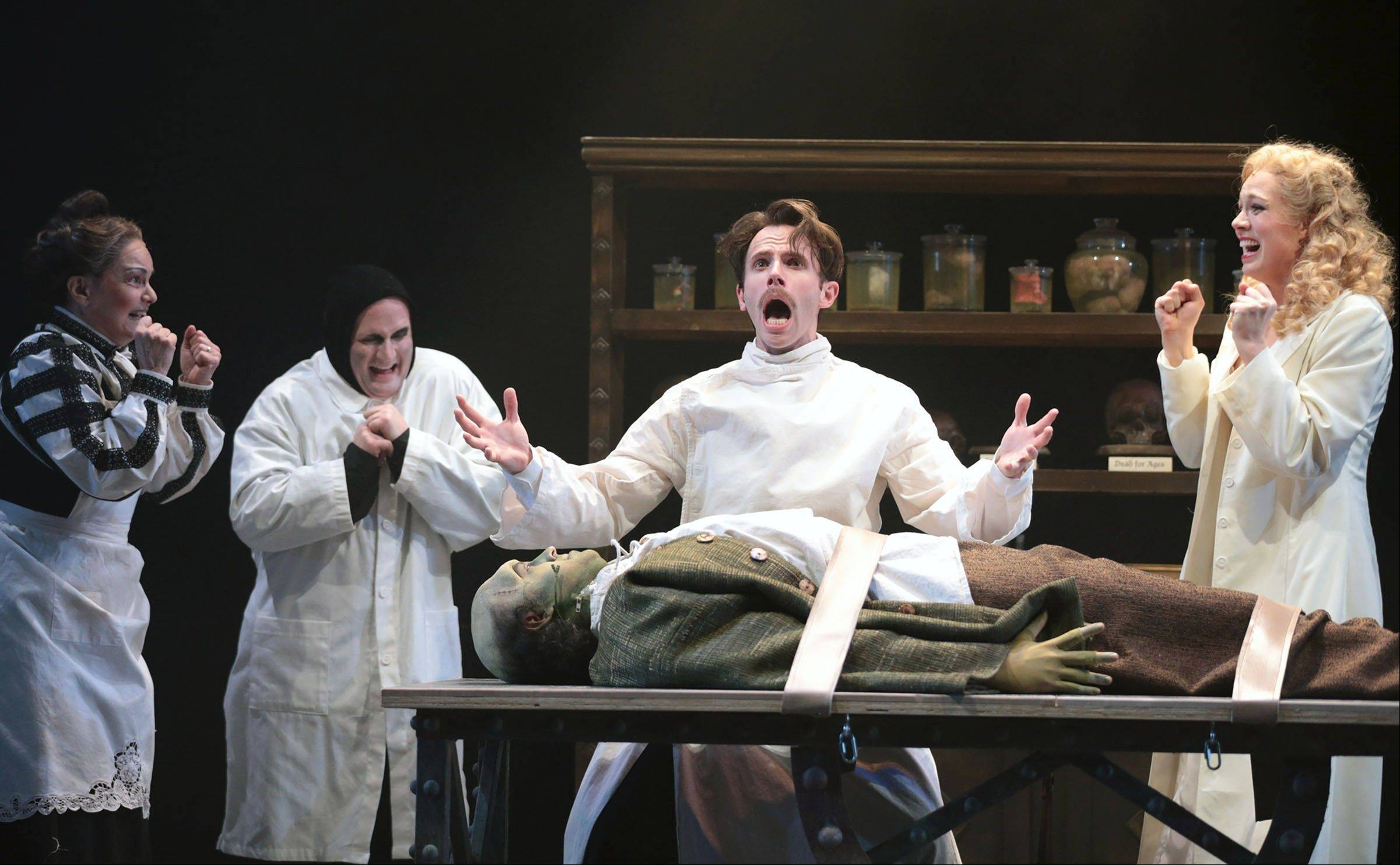 "Dr. Frederick Frankenstein (Devin DeSantis), center, brings his monster (Travis Taylor) to life with help from Frau Blucher (Paula Scrofano), left, Igor (Jeff Dumas) and Inga (Allison Sill) in Drury Lane Theatre's production of ""Young Frankenstein."""