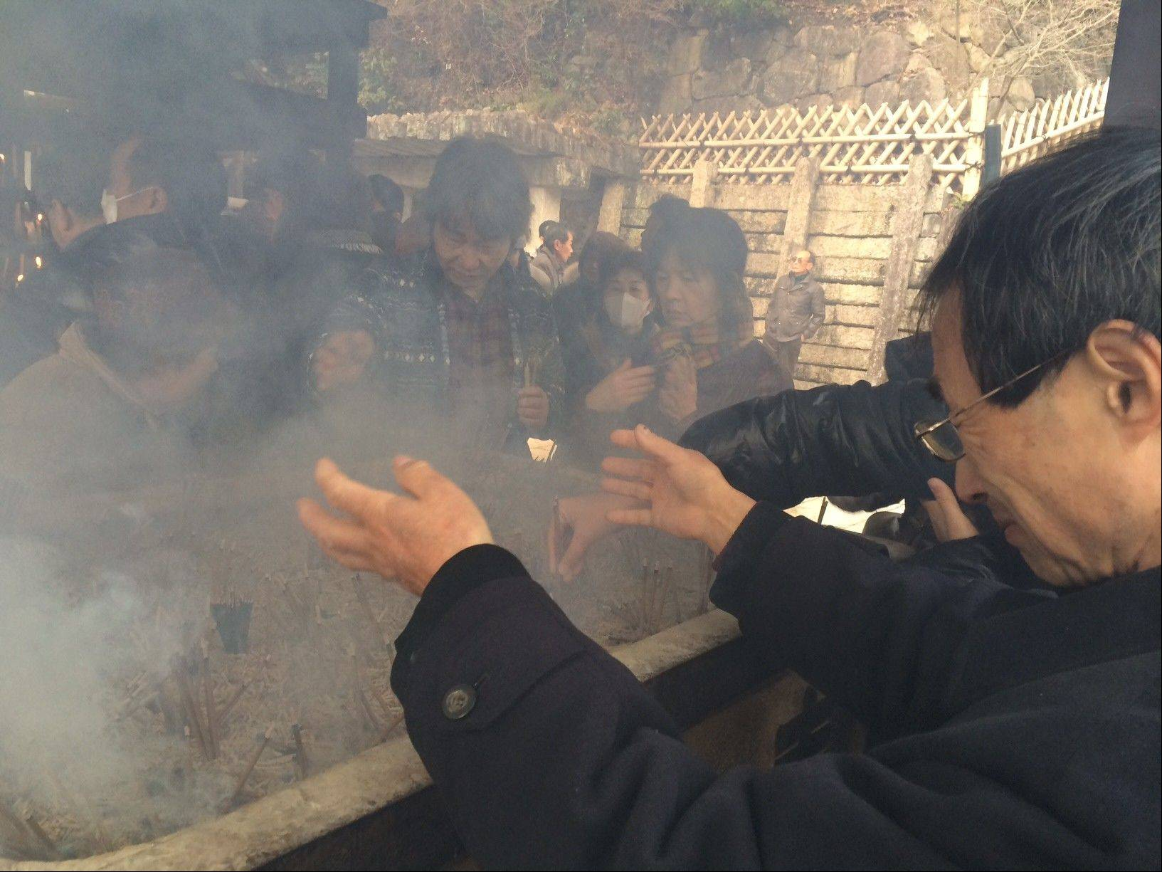 Visitors fan themselves with holy scented smoke from incense burned near the fire god shrine at the Kiyoshikojin Seicho-ji temple complex north of Osaka, Japan.