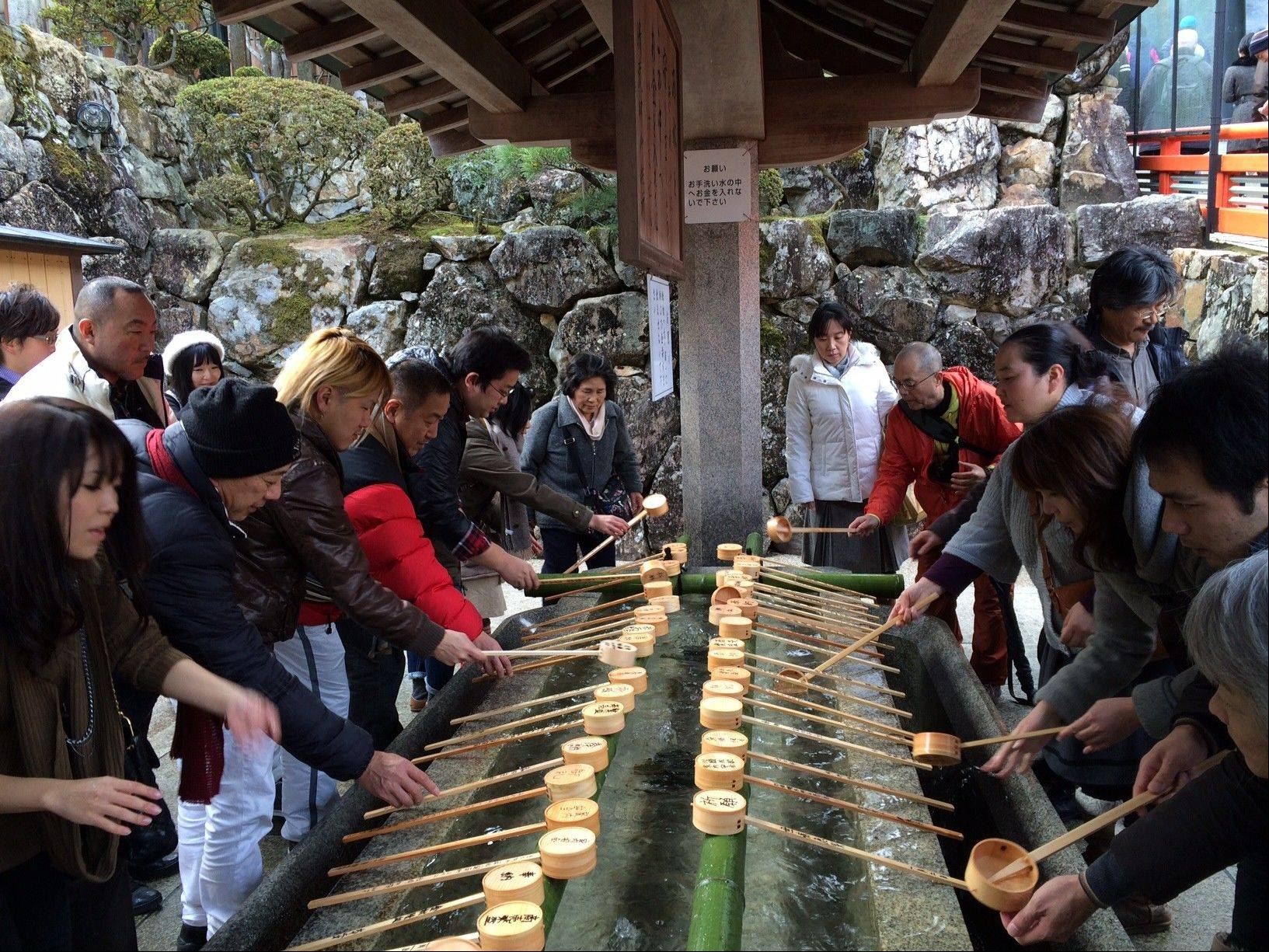 Visitors perform ablutions during a pilgrimage to the Kiyoshikojin Seicho-ji temple complex on a wooded mountain just north of Osaka, Japan. About 3.5 million people visit the complex annually, more than 700,000 of them during the peak pilgrimage season from New Year's to early February.