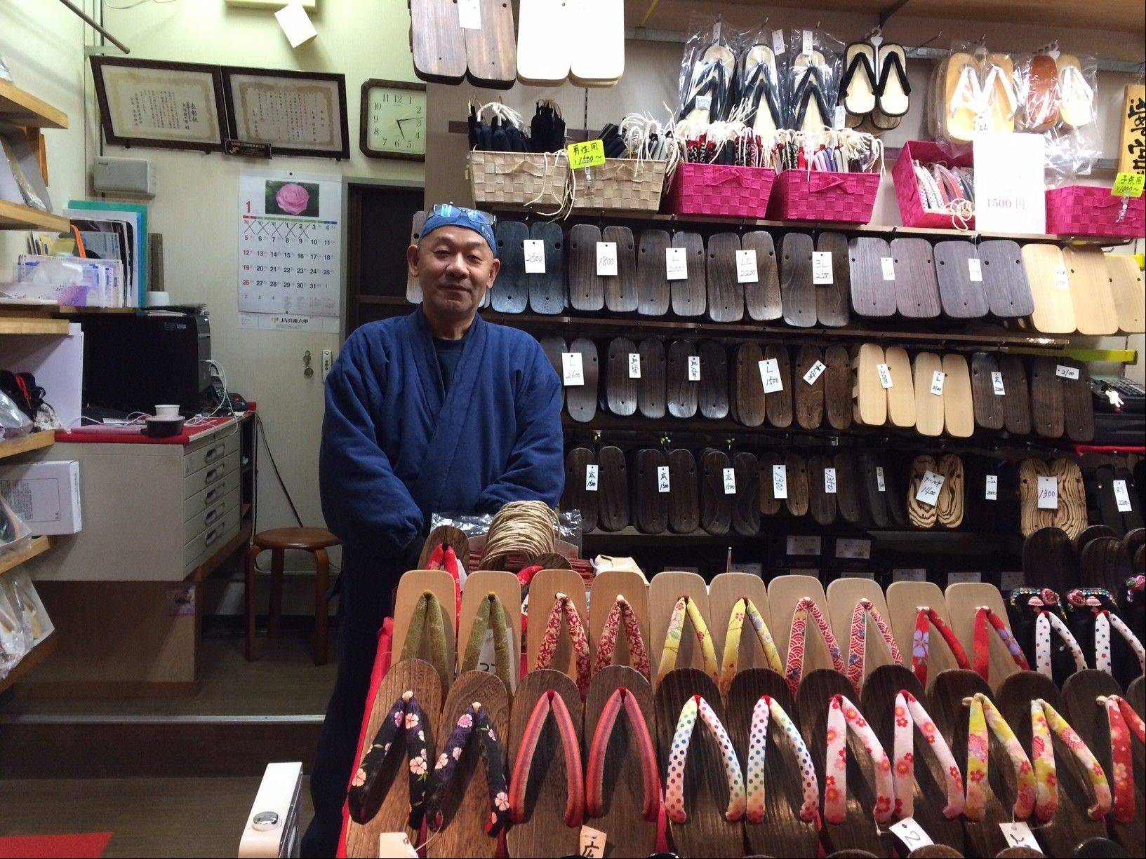 Hiroyuki Oura sells traditional clogs and sandals along the pathway to the shrine of the fire god at the Kiyoshikojin Seicho-ji temple in Japan.