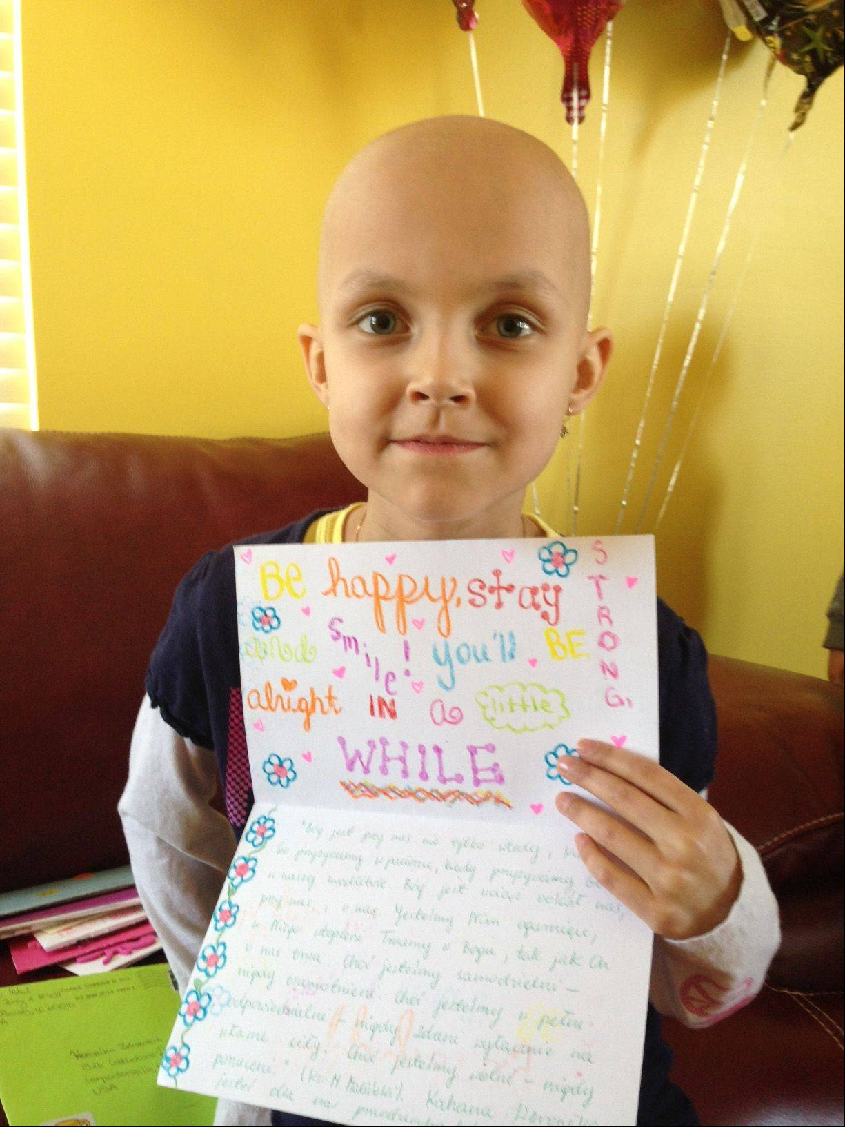 Weronika Zeliszczak, a 7-year-old Carpentersville girl battling leukemia, holds one of the more than 200 cards she received in the mail Tuesday from well wishers. Her mother, Katarzyna Zeliszczak, started a campaign on Facebook encouraging her friends to mail cards to her daughter that congratulate her for completing an intense round of chemotherapy. Weronika hopes to return to school in March.