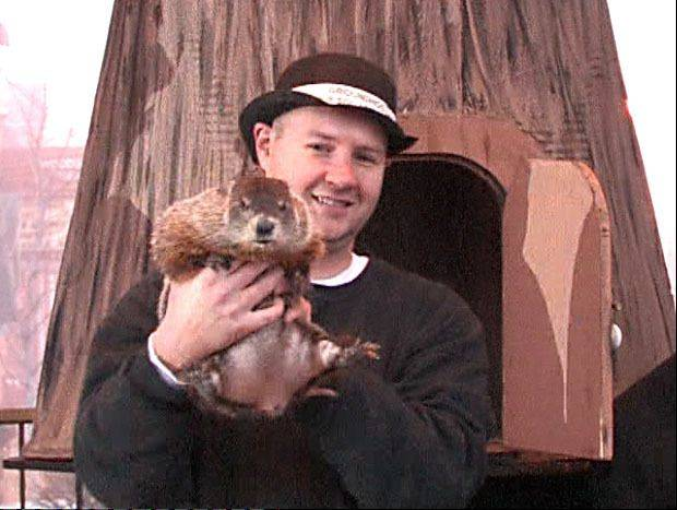Animal handler Mark Szafarn of Chicago brings Woodstock Willie out from the stump to make a seasonal prognostication at a previous Groundhog Days festival.