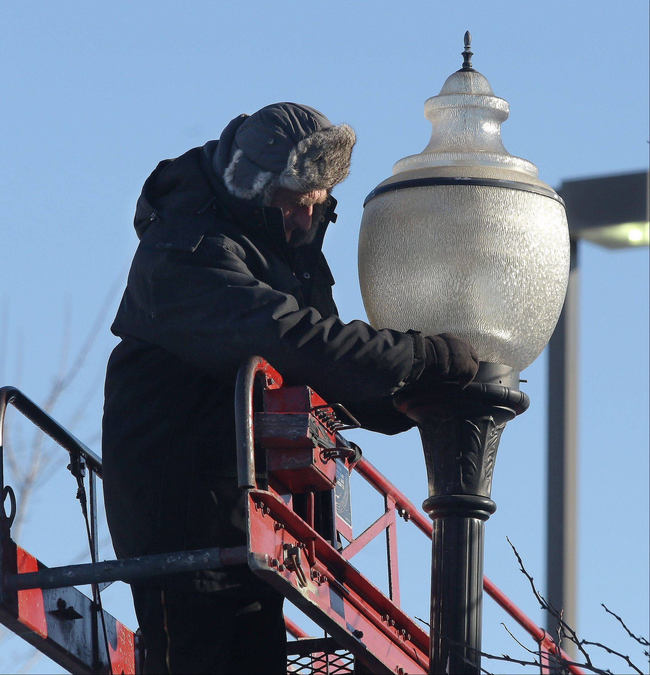 Lighting technician Adam Biernat of Imperial Lighting Maintenance Co. is bundled up as he changes a light bulb in a parking lot in Vernon Hills during subzero temperatures Tuesday.