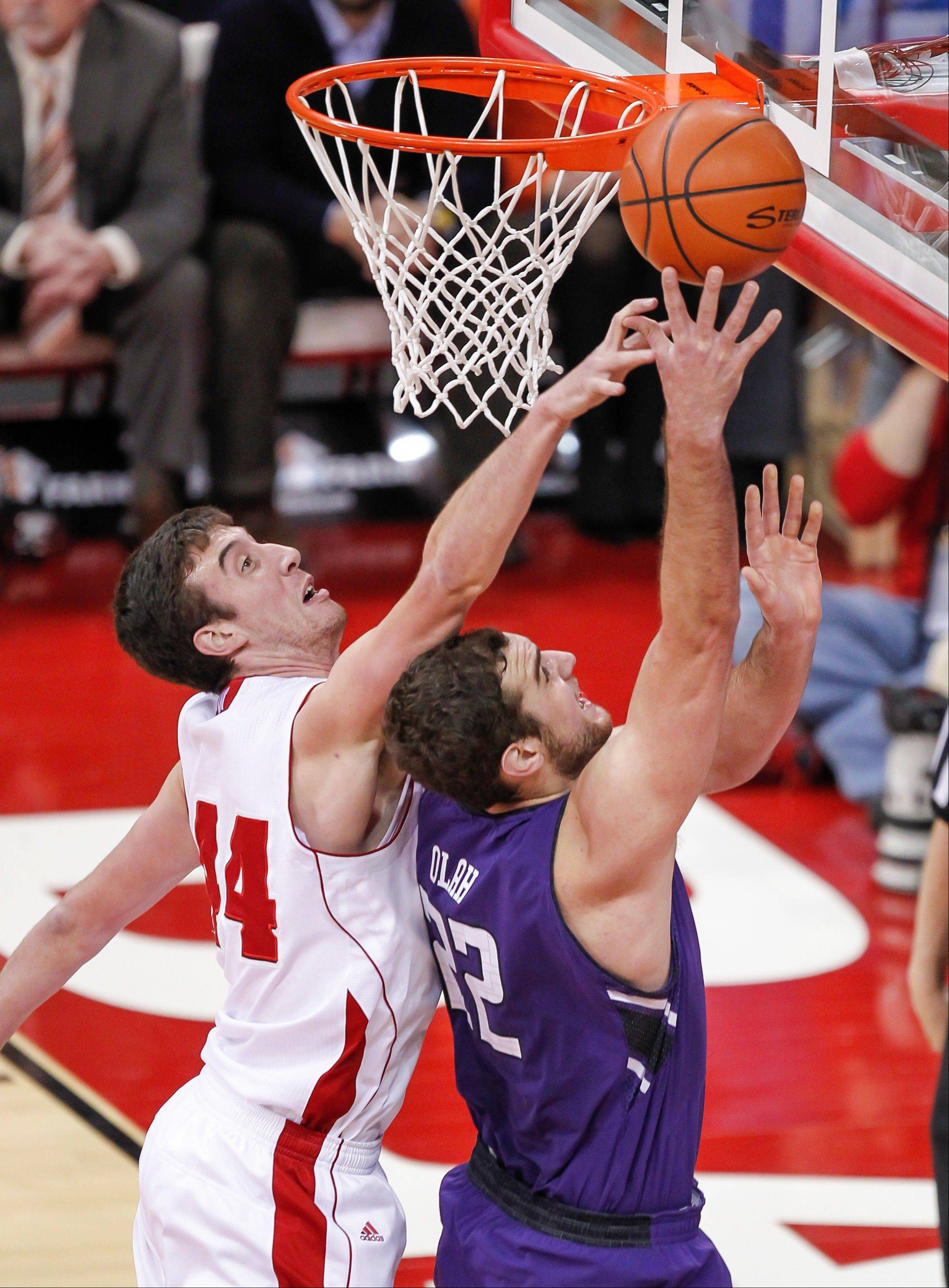 Wisconsin's Frank Kaminsky, left, knocks the ball away from Northwestern's Alex Olah during the first half of Wednesday's game in Madison, Wis.