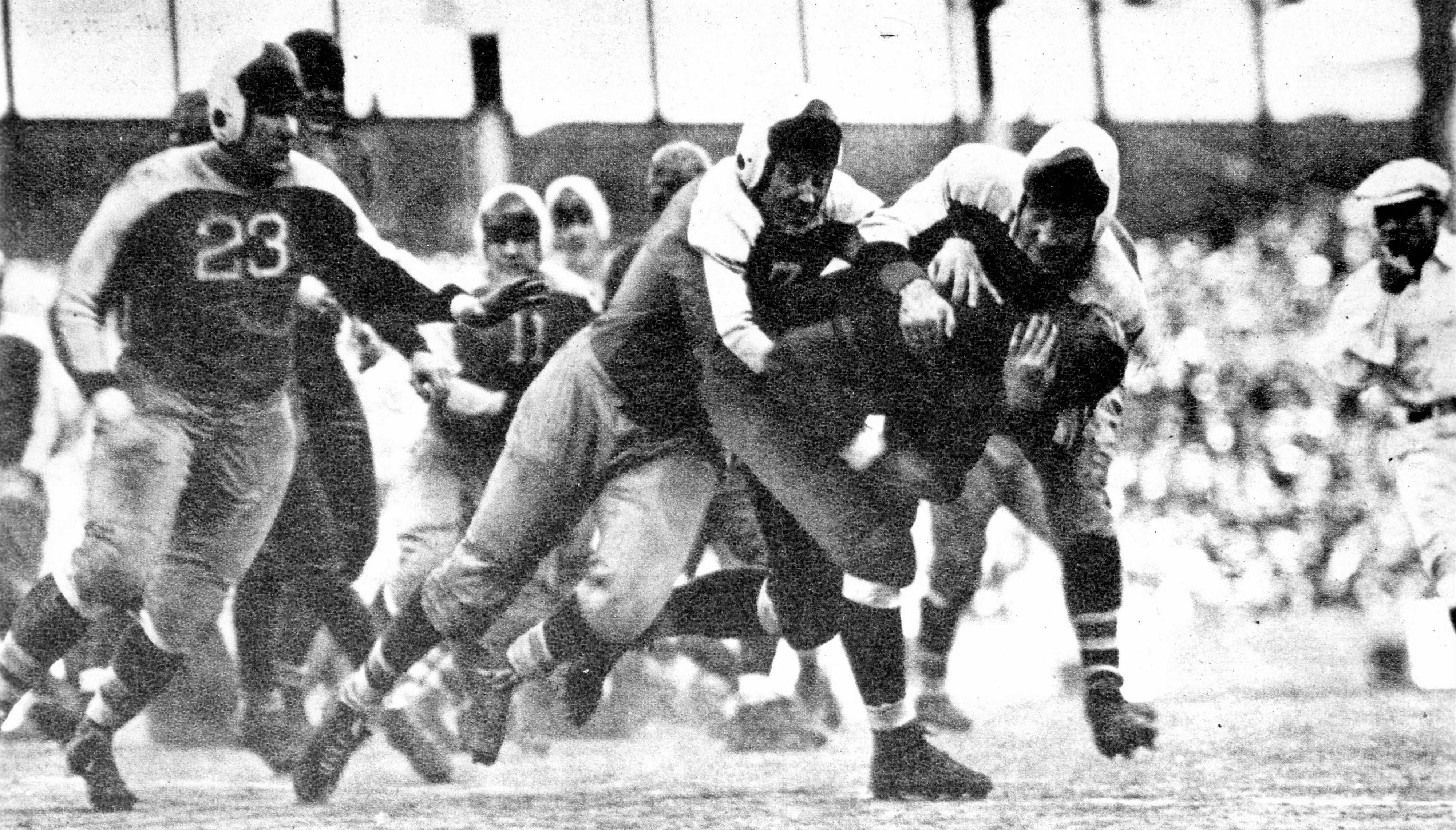 In this photo taken on Dec. 9, 1934, and released by the Pro Football Hall of Fame, Chicago Bears fullback Bronko Nagurski is tackled by New York Giants' Mel Hein during a Giants' 30-13 victory over the Bears in the NFL Championship game at the Polo Grounds in New York.