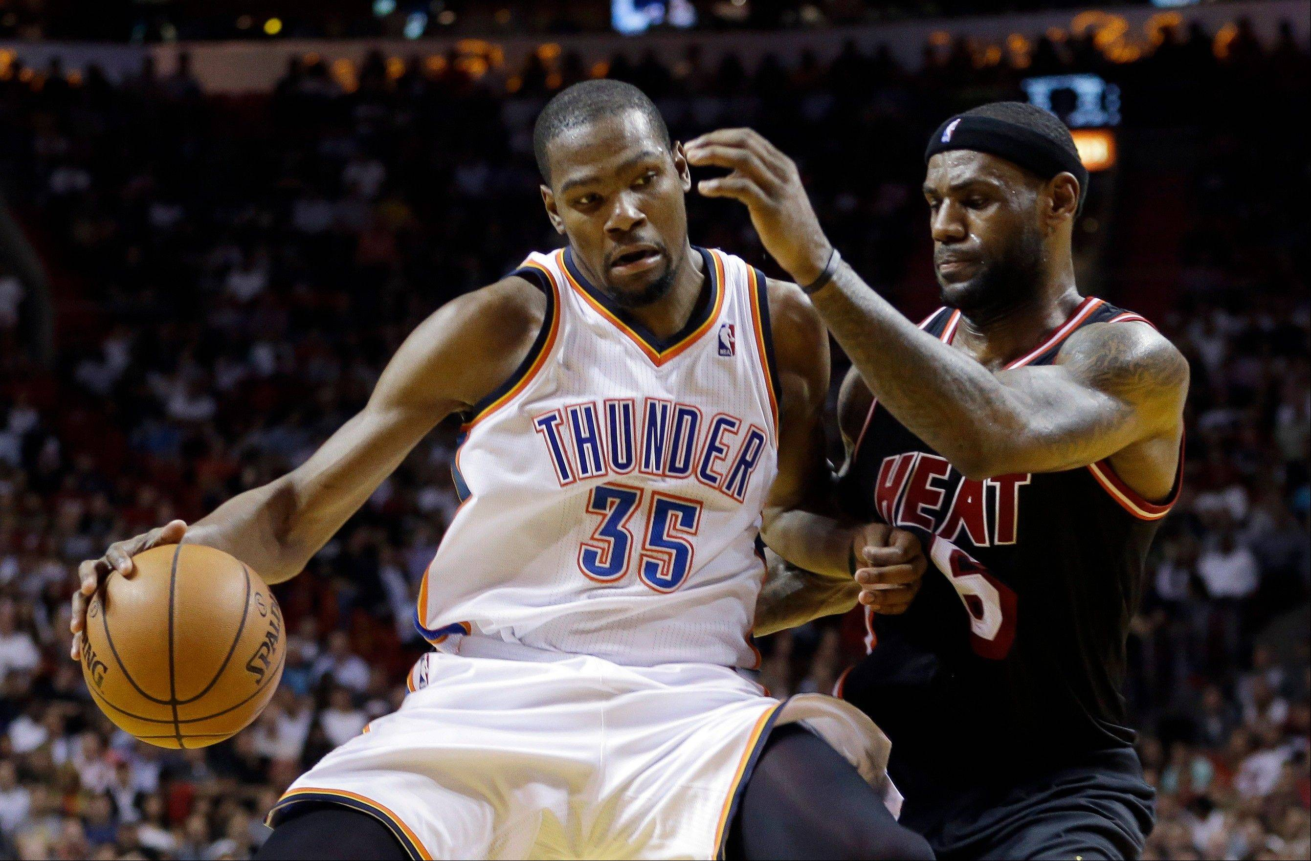 Miami Heat small forward LeBron James (6) puts pressure on Oklahoma City Thunder small forward Kevin Durant (35) during the fourth period of an NBA basketball game in Miami, Wednesday, Jan. 29, 2014. The Thunder won 112-95.