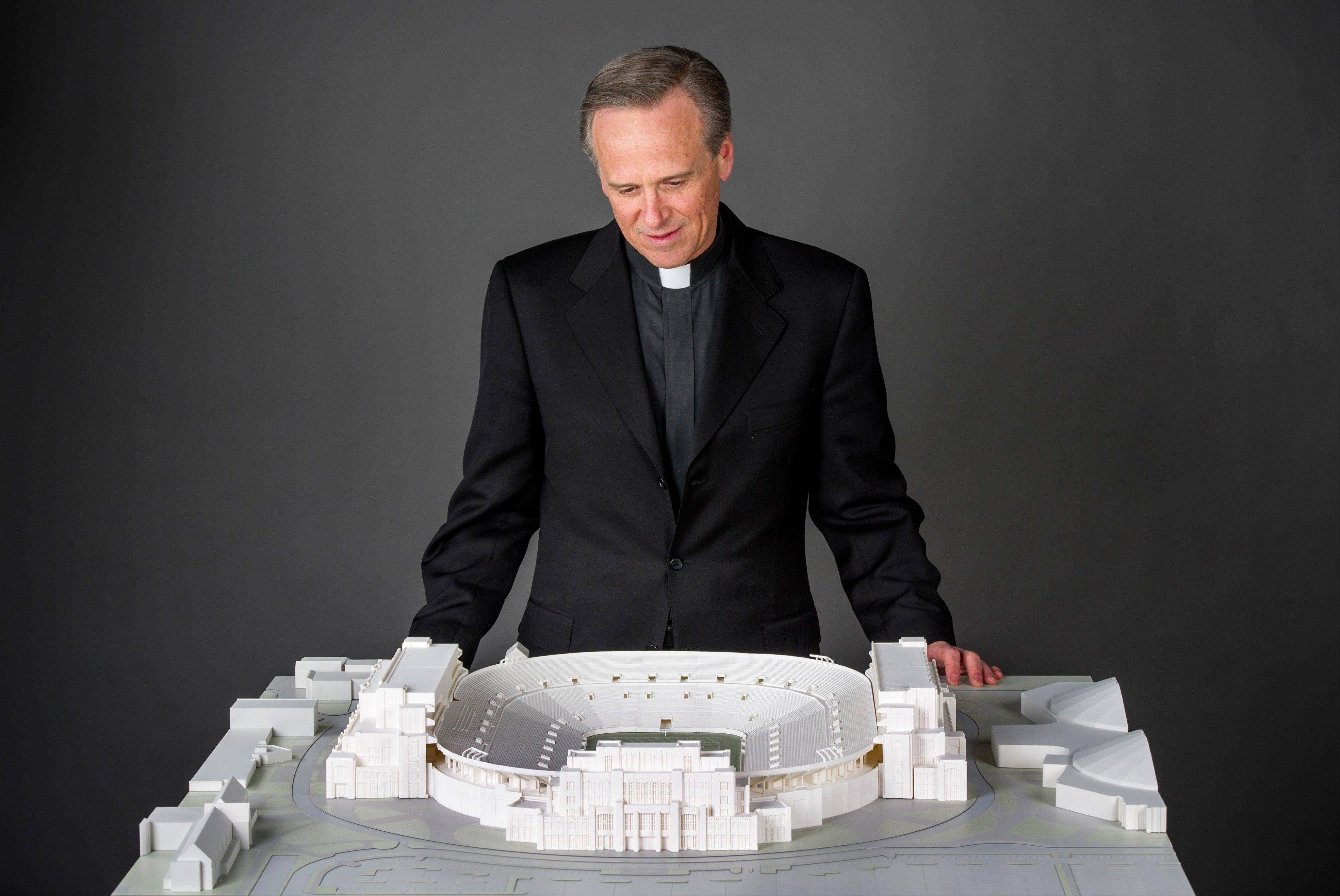 In this Jan. 19, 2014 photo University of Notre Dame president, Rev. John I. Jenkins, C.S.C., looks at a model of the school's new football stadium. Notre Dame announced plans Wednesday, Jan. 29, 2014 to expand the schoolís 84-year-old football stadium, adding up to 4,000 premium seats and spending about $400 million to add buildings on three sides of the ìHouse that Rockne Built.î