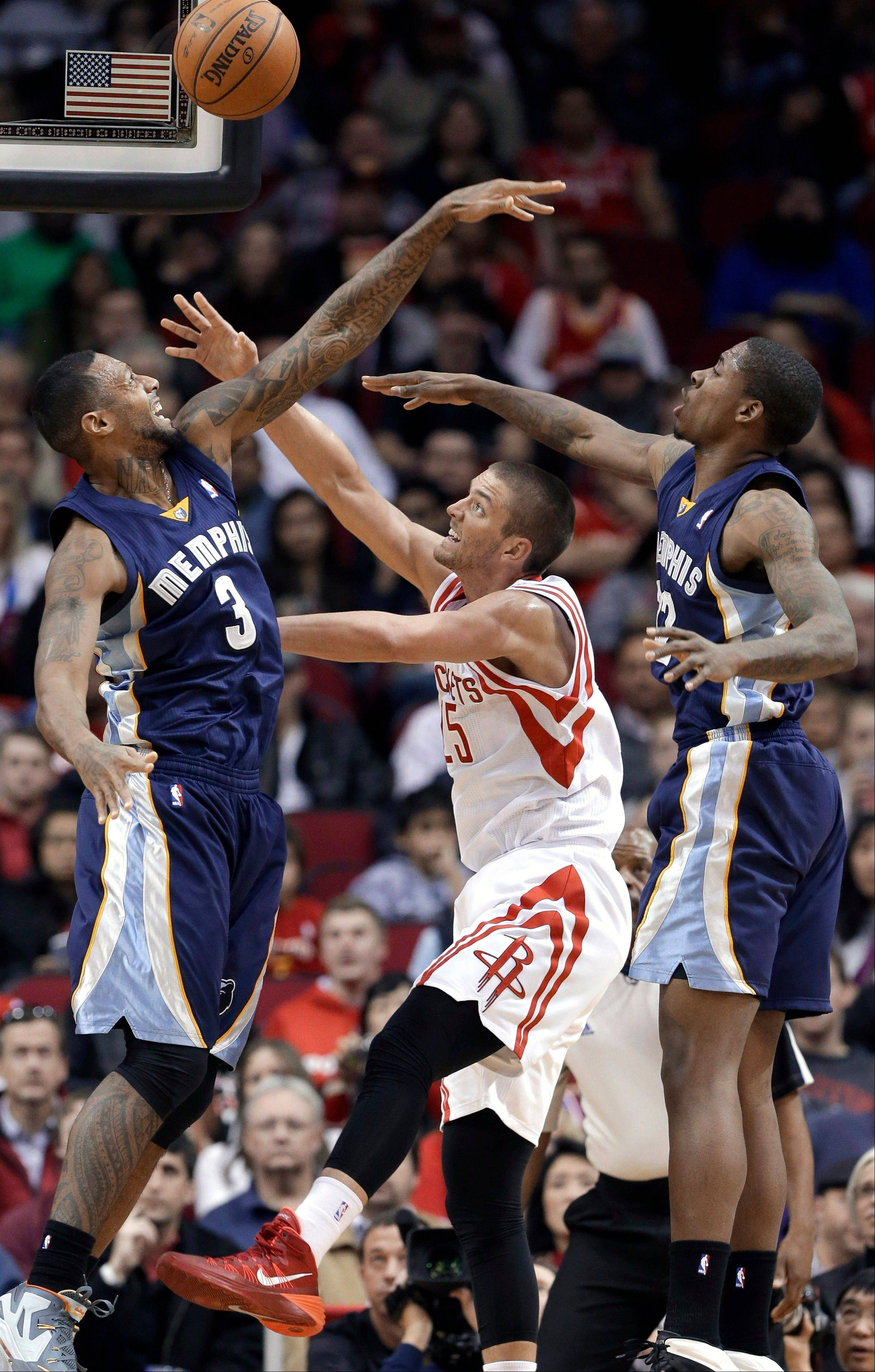Houston Rockets' Chandler Parsons (25) is double-teamed by Memphis Grizzlies' James Johnson (3) and Ed Davis during the first half of an NBA basketball game Friday, Jan. 24, 2014, in Houston.
