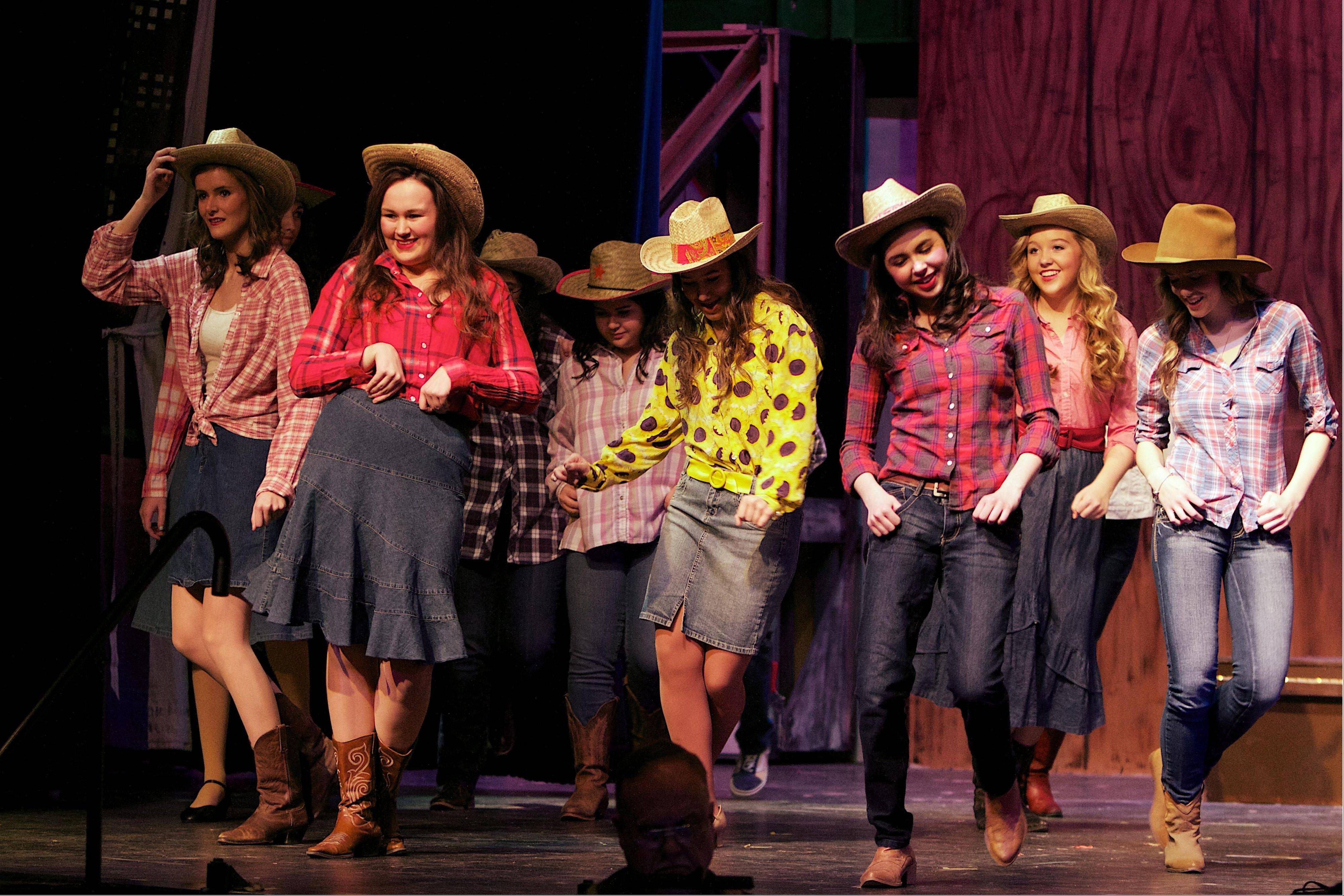 "Seniors Jennifer Brandt, left, and Mary Hanisch, both of Arlington Heights, join the rest of the ensemble in the ""Footloose"" number ""Let's Hear it for the Boy."""