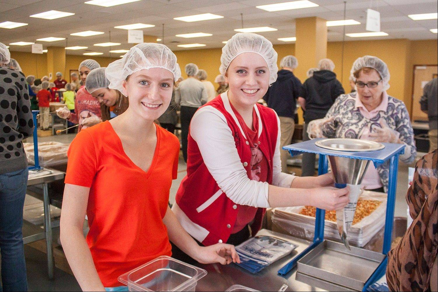 Woodlands Academy of the Sacred Heart students Elizabeth, left, and Laura Bartusiak of Lake Forest were among the volunteers who packed meals at Feed My Starving Children in Libertyville.