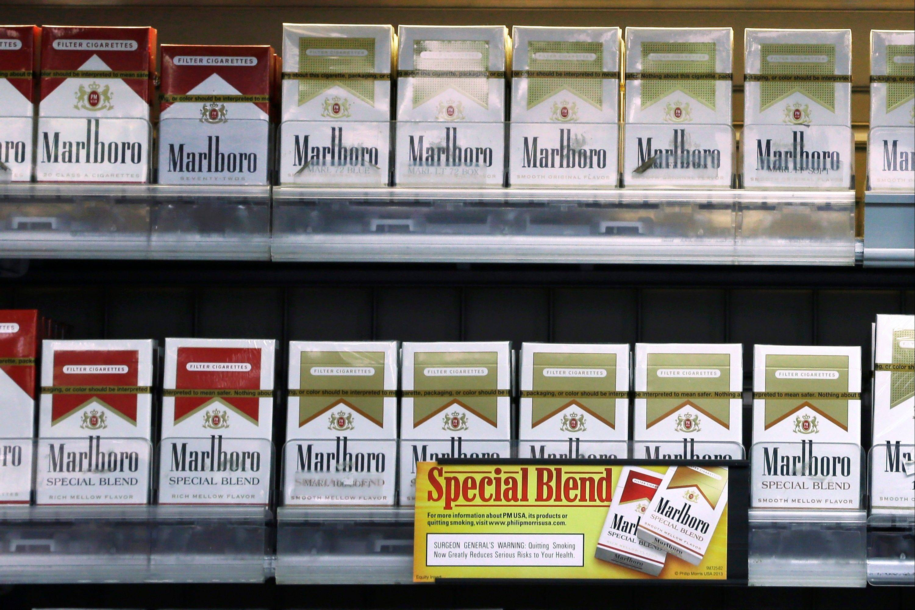 Altria Group Inc.'s fourth-quarter profit dropped 56 percent as the Marlboro maker sold fewer cigarettes and recorded charges related to paying off debt early.
