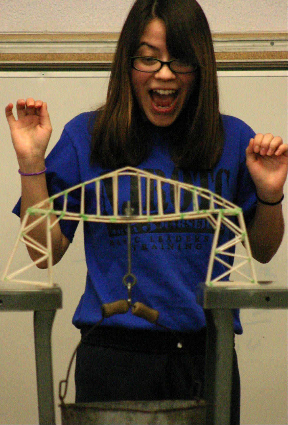 Rocio Sanchez celebrates after adding weight during the recent Mooseheart Bridge Breaking Contest. Sanchez´s bridge broke shortly after, having withstood 9 pounds, and earning the senior second place.