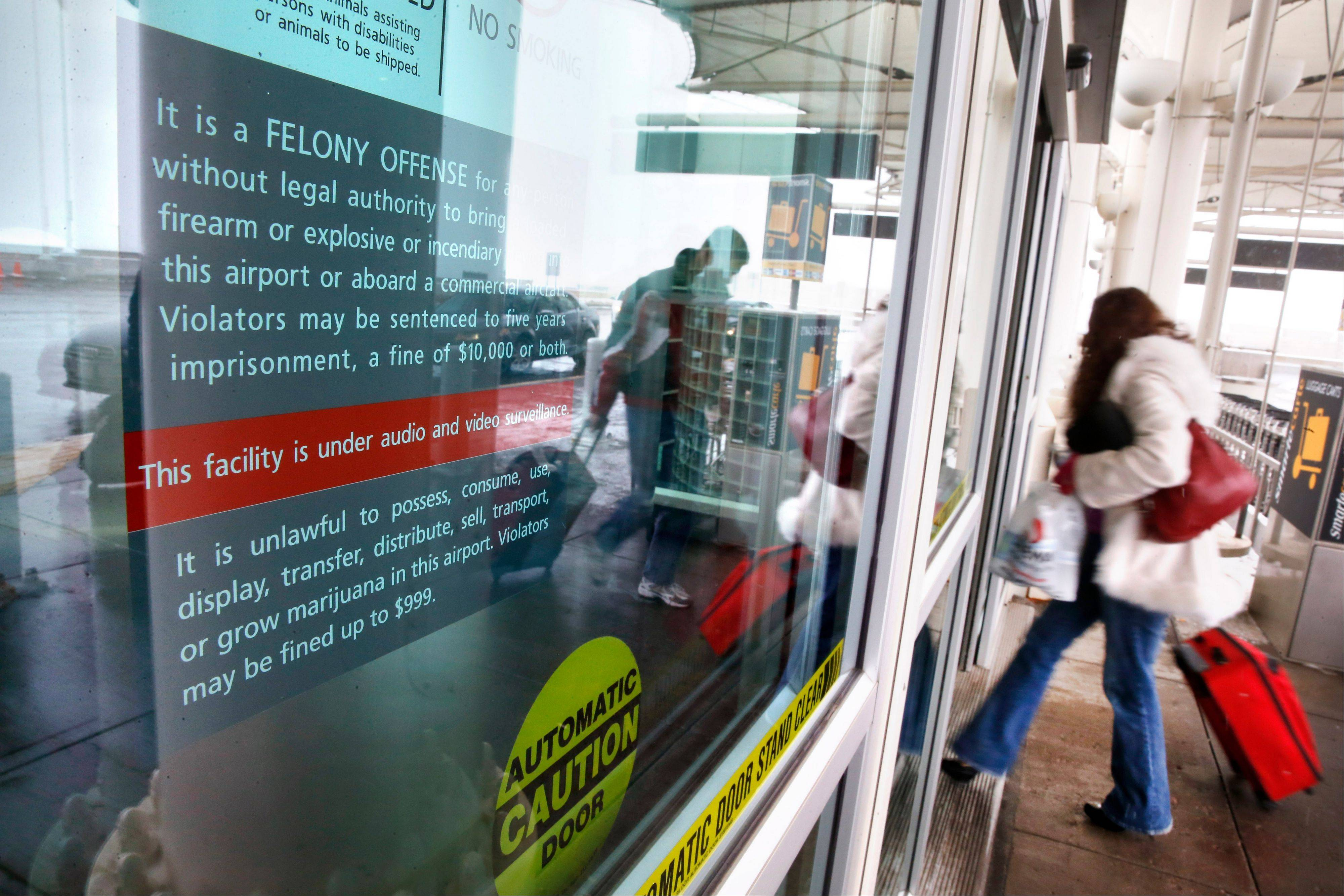 A woman enters Denver International Airport, passing a notice prohibiting marijuana possession at the airport, Monday, Jan. 27, 2014. Carrying marijuana through airport security in Colorado may get the pot confiscated, but there appears to be little danger of legal repercussions.