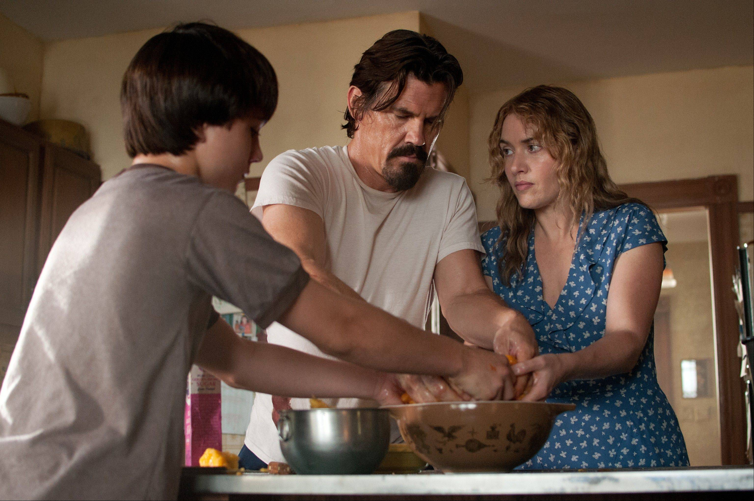 "Henry (Gattlin Griffith), left, Frank (Josh Brolin) and Adele (Kate Winslet) work the dough for a perfect pie crust in ""Labor Day,"" a middle-aged extension of an adolescent girl's bad-boy fantasy."