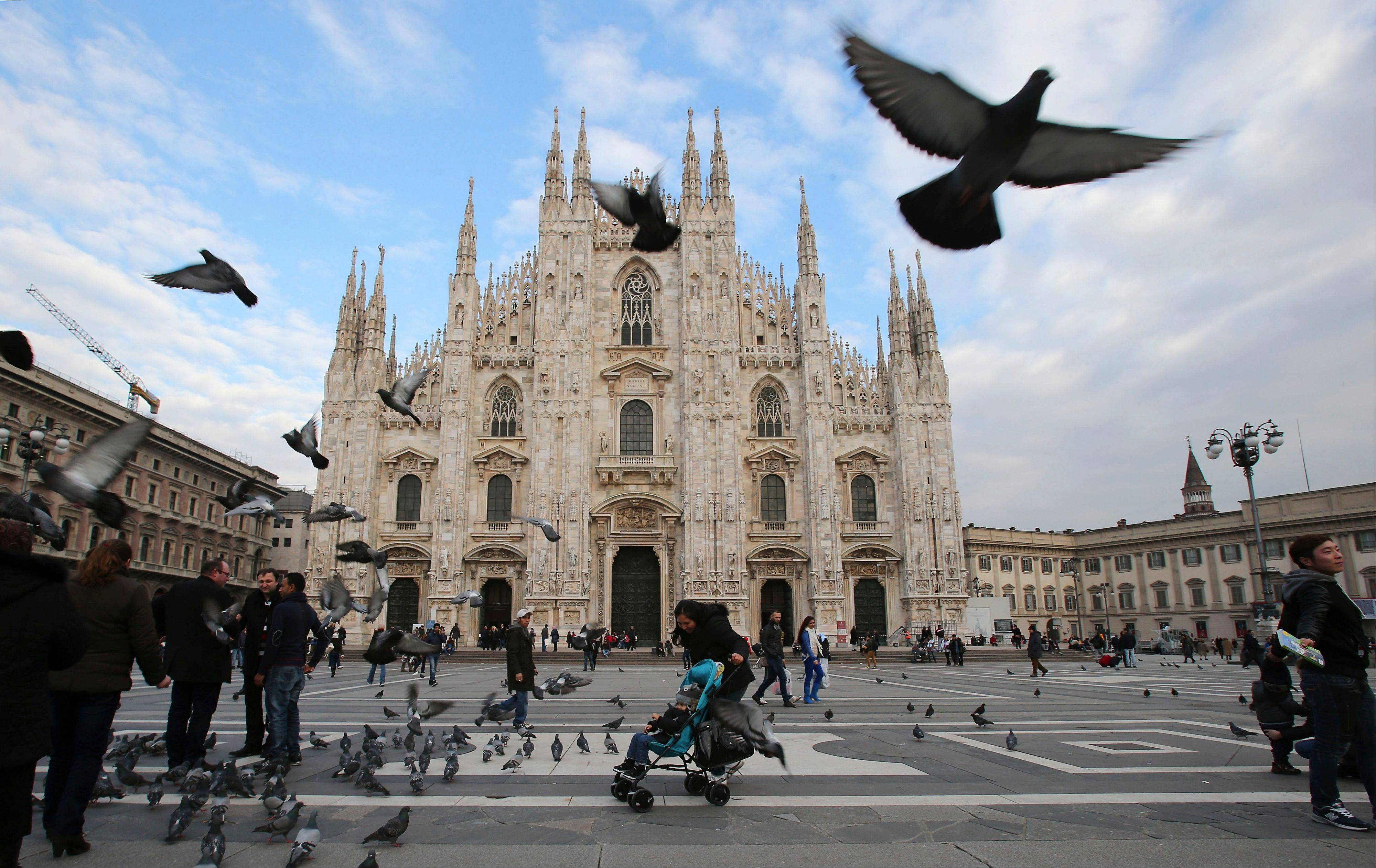 Visitors dodge birds in the piazza outside of the Duomo cathedral in Milan, Italy. The ornate white facade of Milan's Duomo is the single most recognized symbol of the Lombard capital, taking centuries to complete.