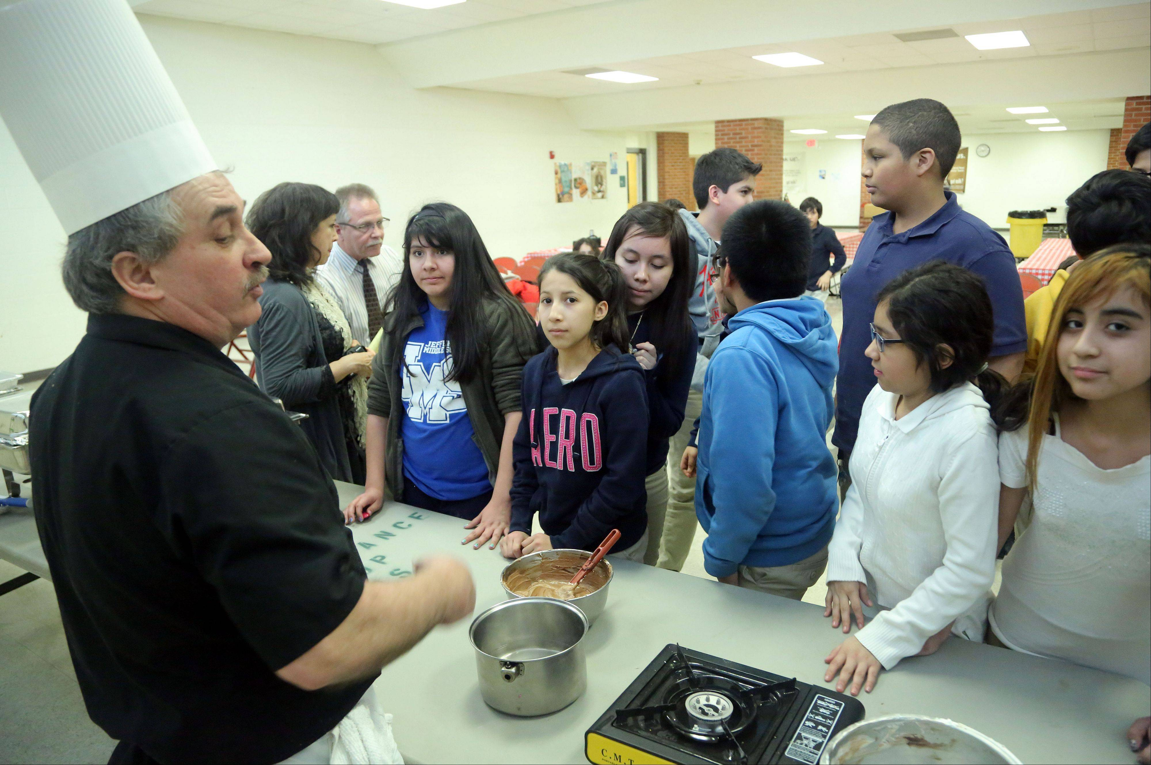 Claude Bouteille, left, owner/chef of Taste of Paris Restaurant in Mundelein, teaches kids how to make chocolate mousse Thursday during a demonstration for sixth-, seventh- and eight-graders in Maureen Fischer Rivkin's French class at Thomas Jefferson School in Waukegan.