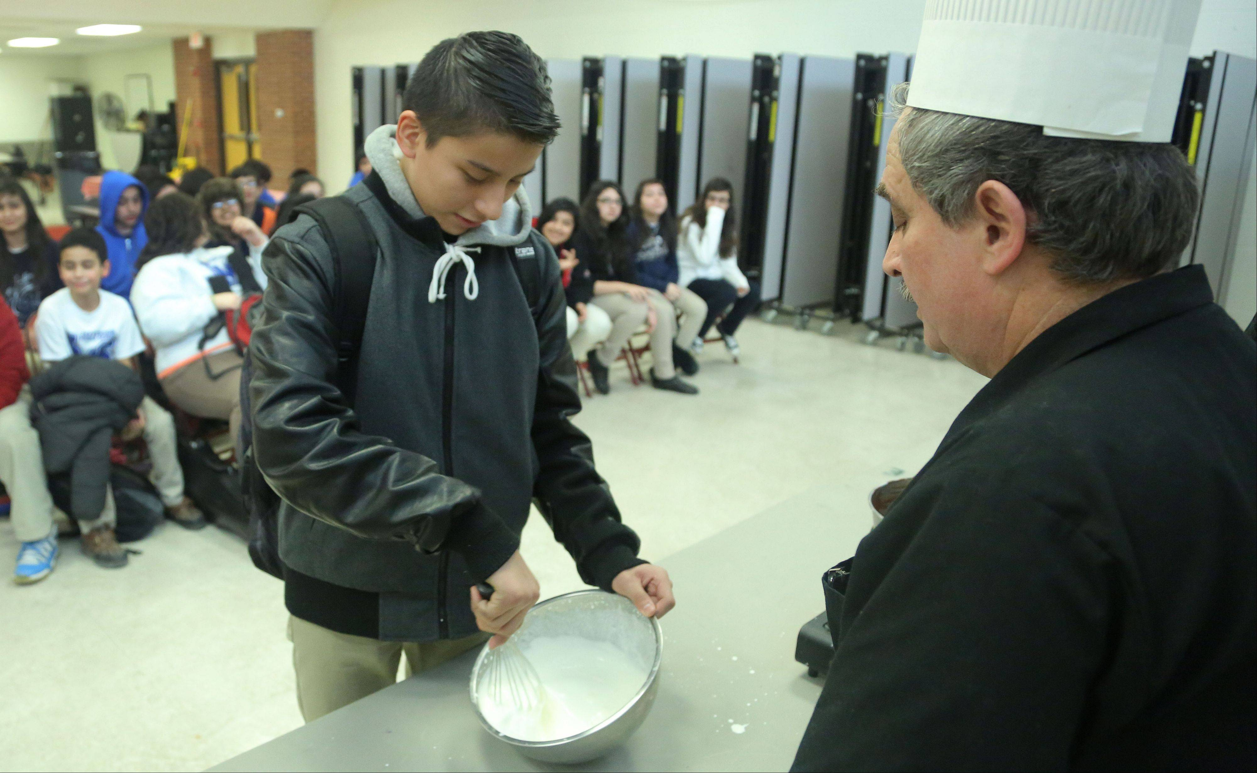 Seventh-grader Andy Estrada, left, learns how to whip cream as Claude Bouteille, owner/chef of Taste of Paris Restaurant in Mundelein, gave a French cooking demonstration Thursday for sixth-, seventh- and eighth-graders in Maureen Fischer Rivkin's French class at Thomas Jefferson School in Waukegan.