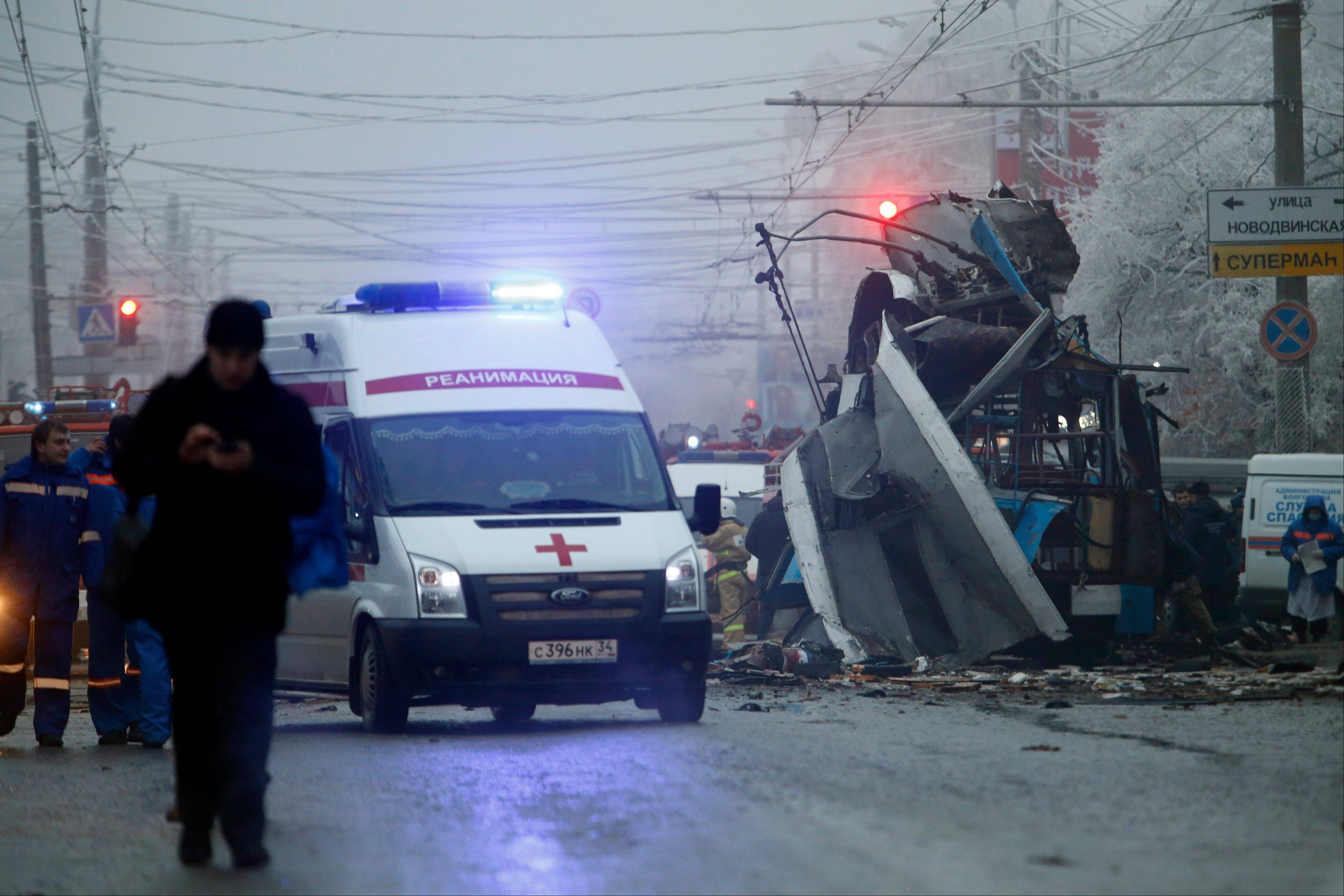 An ambulance leaves the site of an explosion after a bomb blast tore through a trolley bus, background, in the city of Volgograd on Dec. 30, 2013. Russia's counter terrorism agency on Thursday identified the two suicide bombers who struck Volgograd and announced the arrest of two suspected accomplices.