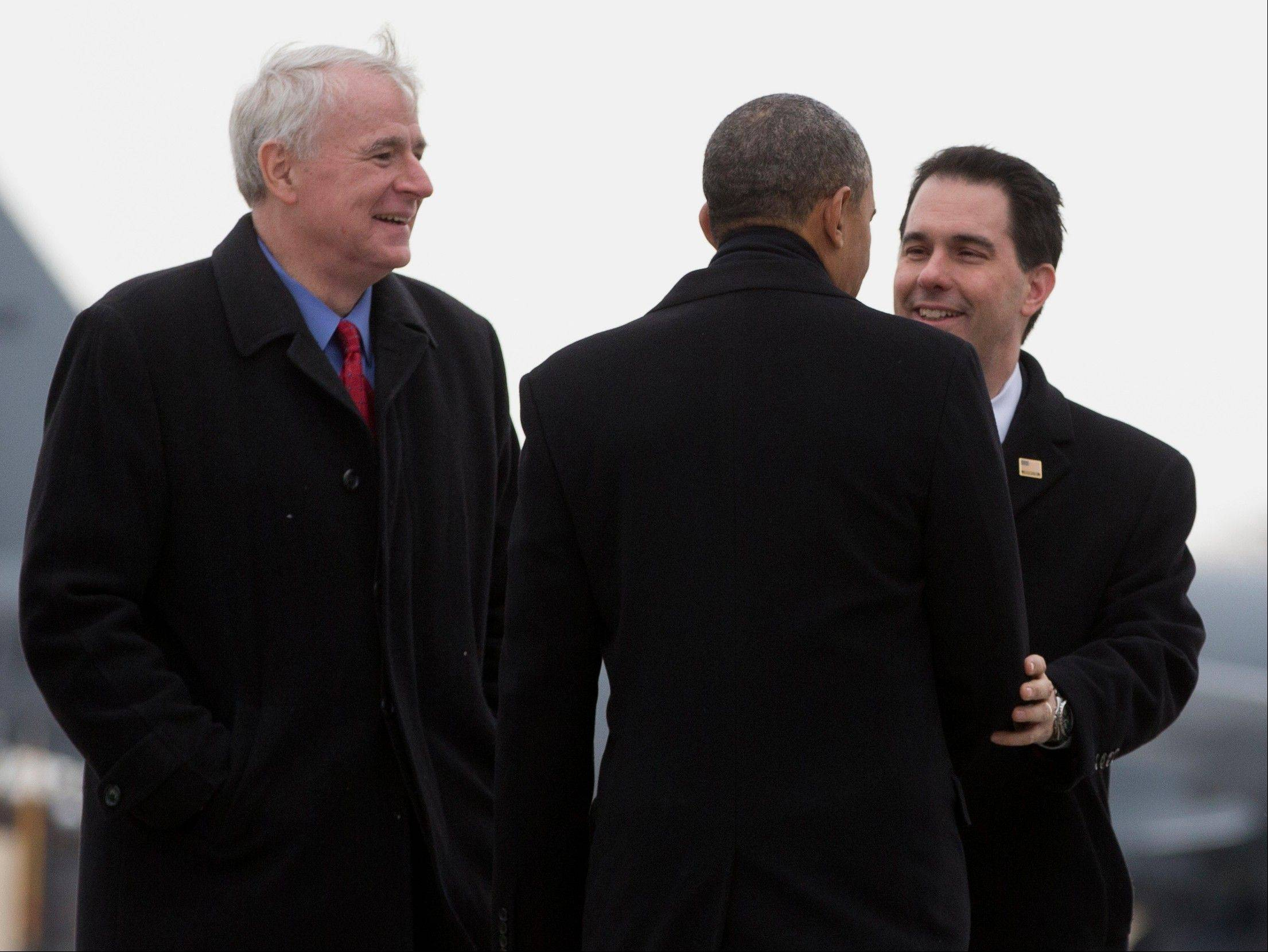 President Barack Obama is greeted by Wis. Gov. Scott Walker, right, and Milwaukee Mayor Tom Barrett as he steps from Air Force One upon his arrival at the Wisconsin Air National Guard 128th Air Refueling Wing in Milwaukee. He will speak at General Electricís Waukesha Gas Engines facility in Waukesha, Wis., about job training.
