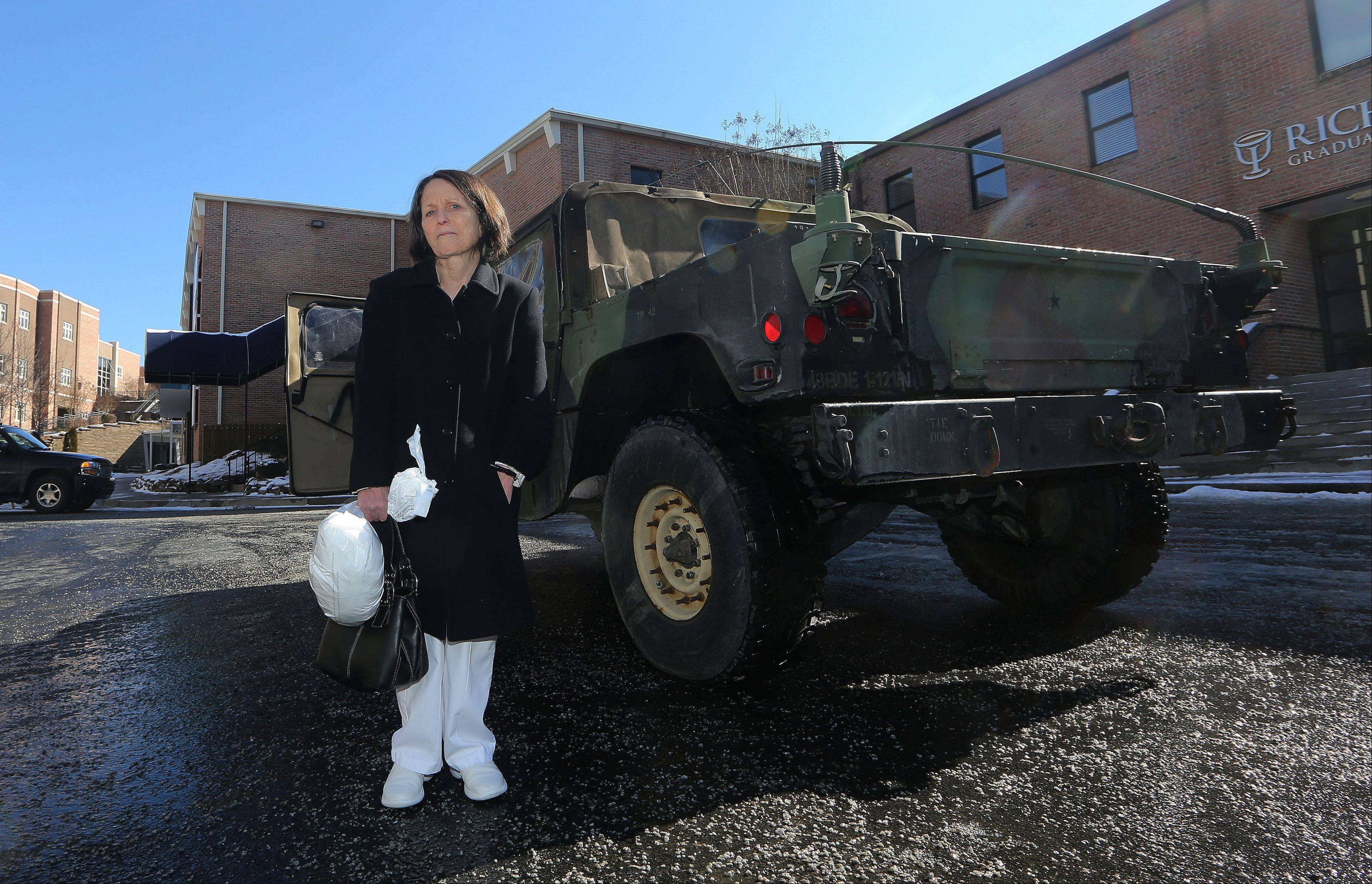Lila Gunter waits next to a Georgia National Guard vehicle before they take her to pick up her car after it was towed in the winter storm that swept across the state Thursday, Jan. 30, 2014, in Atlanta. The Guard and the Georgia State Patrol are offering rides to motorist who had in abandon their cars.