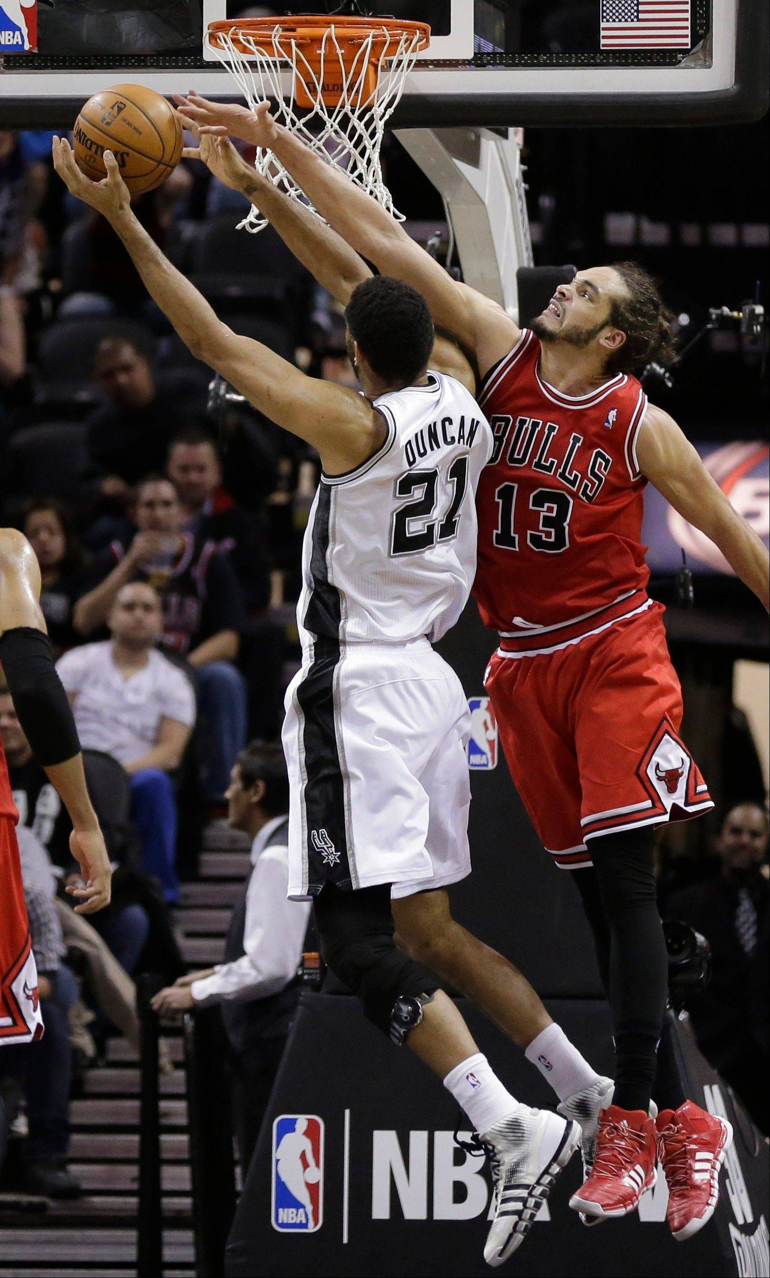 San Antonio Spurs' Tim Duncan (21) goes to the basket against Chicago Bulls' Joakim Noah (13) during the second half of an NBA basketball game, Wednesday, Jan. 29, 2014, in San Antonio. Chicago won 96-86.