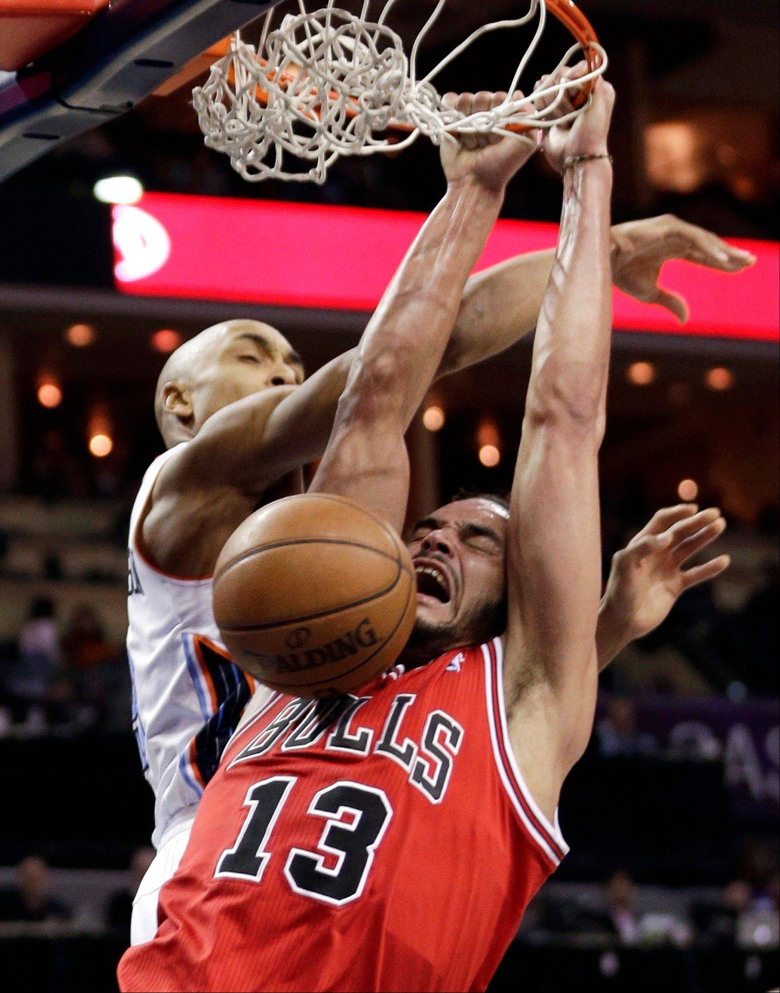 Chicago Bulls' Joakim Noah (13) dunks against Charlotte Bobcats' Gerald Henderson during the second half of an NBA basketball game in Charlotte, N.C., Saturday, Jan. 25, 2014. The Bulls won 89-87.